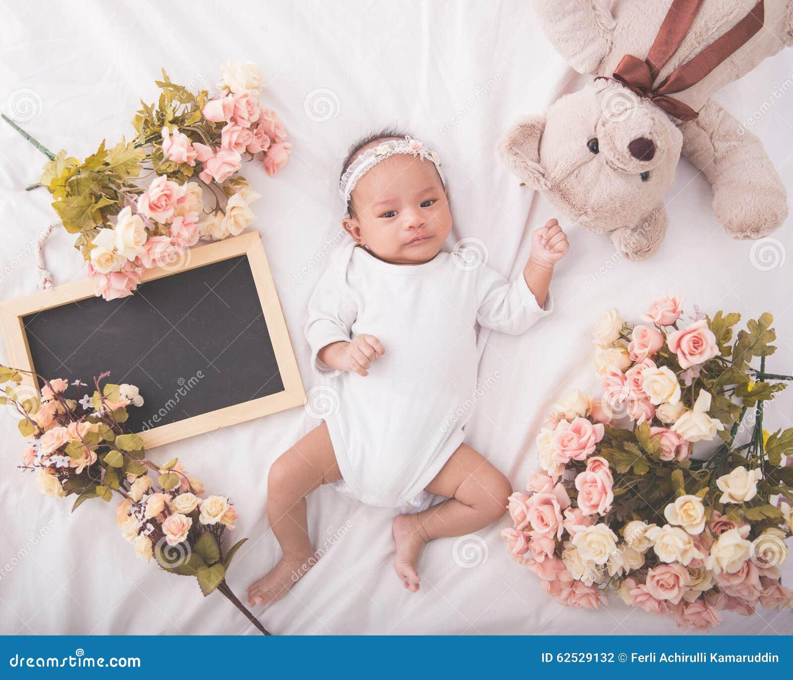 白色毯子的逗人喜爱的亚裔女婴在空白的黑板旁边,