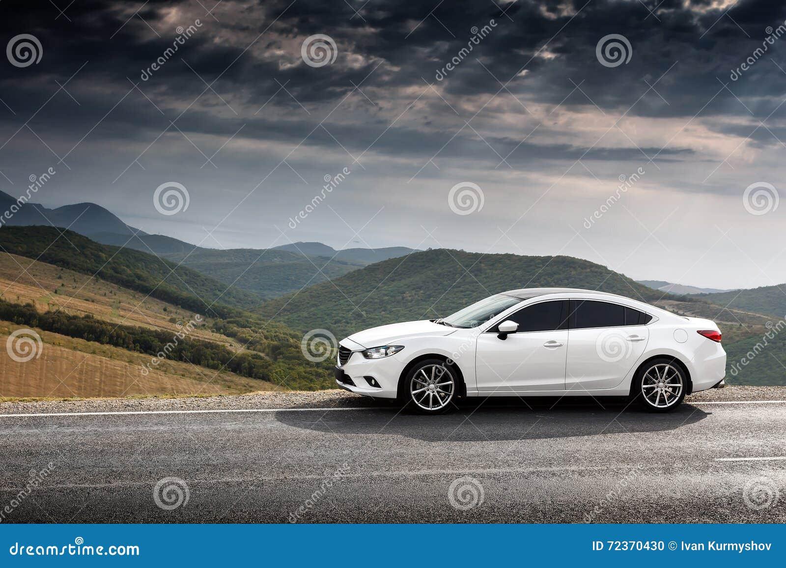 白色汽车停放了在乡下柏油路靠近绿色山