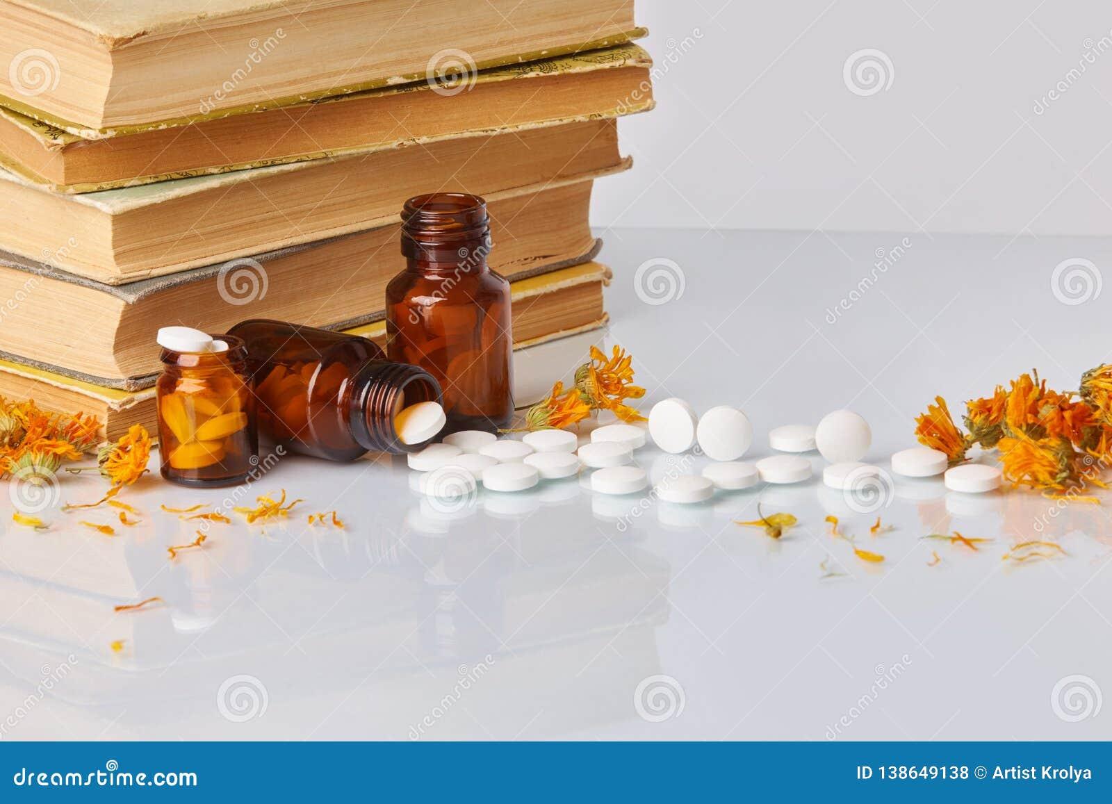 白色片剂和药片与万寿菊金盏草和旧书在白色镜子背景