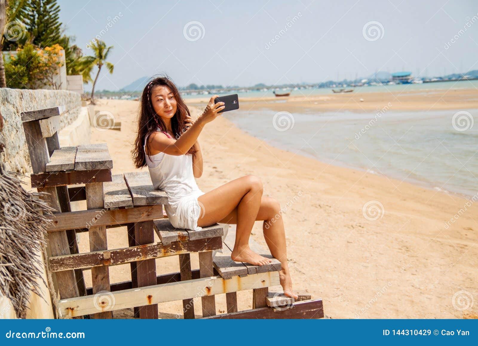 白色礼服的美丽的亚裔妇女在海滩做selfie