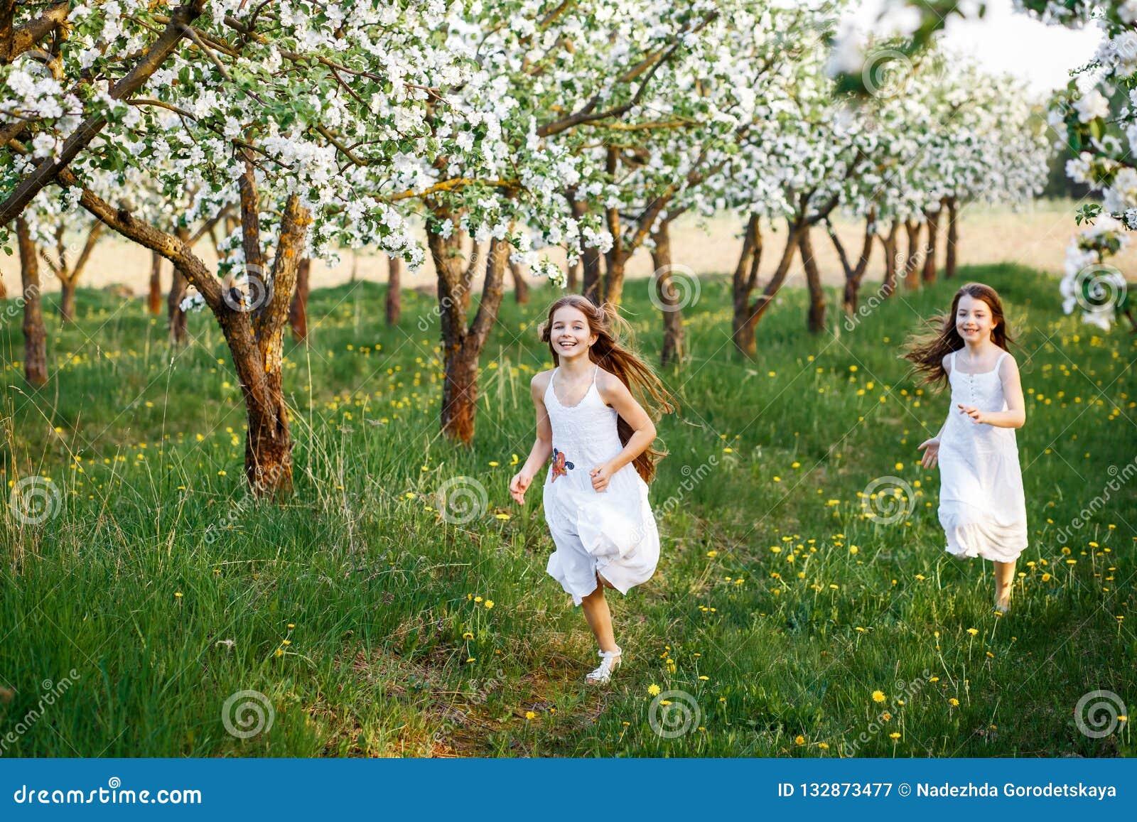 白色礼服的美丽的少女在有blosoming在日落的苹果树的庭院里 拥抱二的朋友