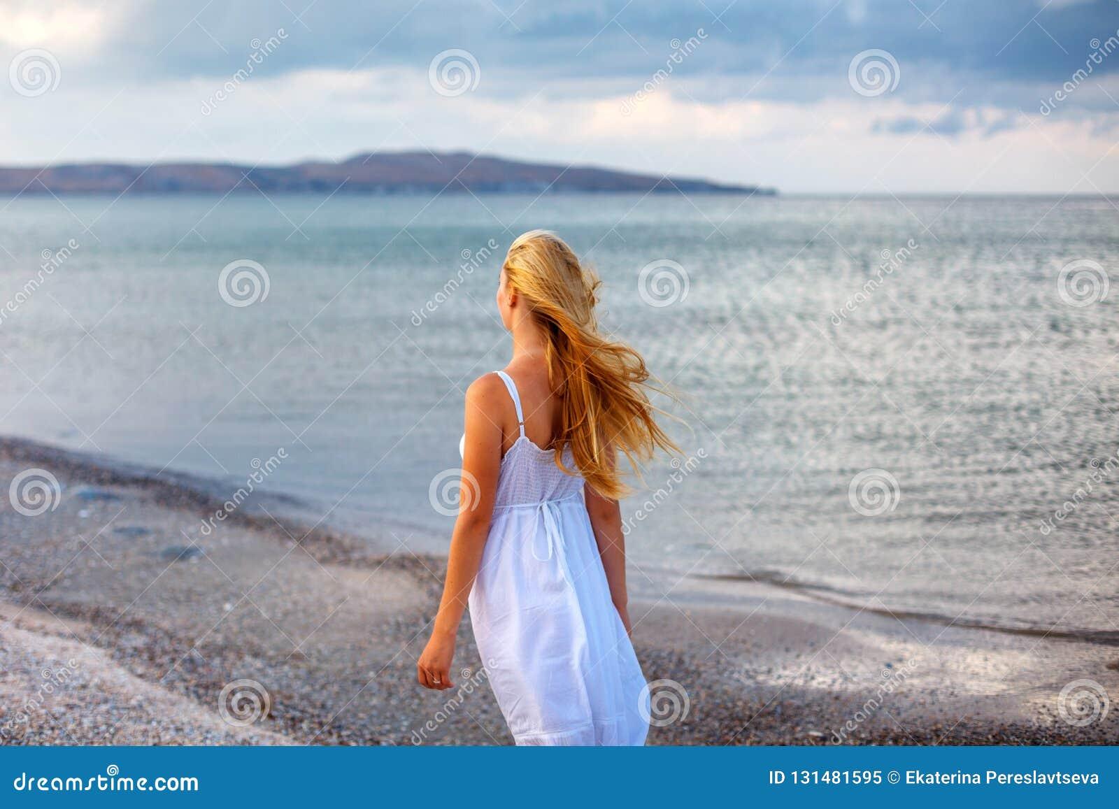 白色礼服的美丽的年轻女人由海在阳光下