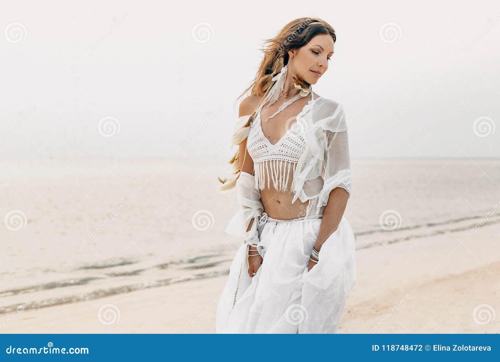 白色礼服的美丽的年轻boho摆在妇女和的羽毛