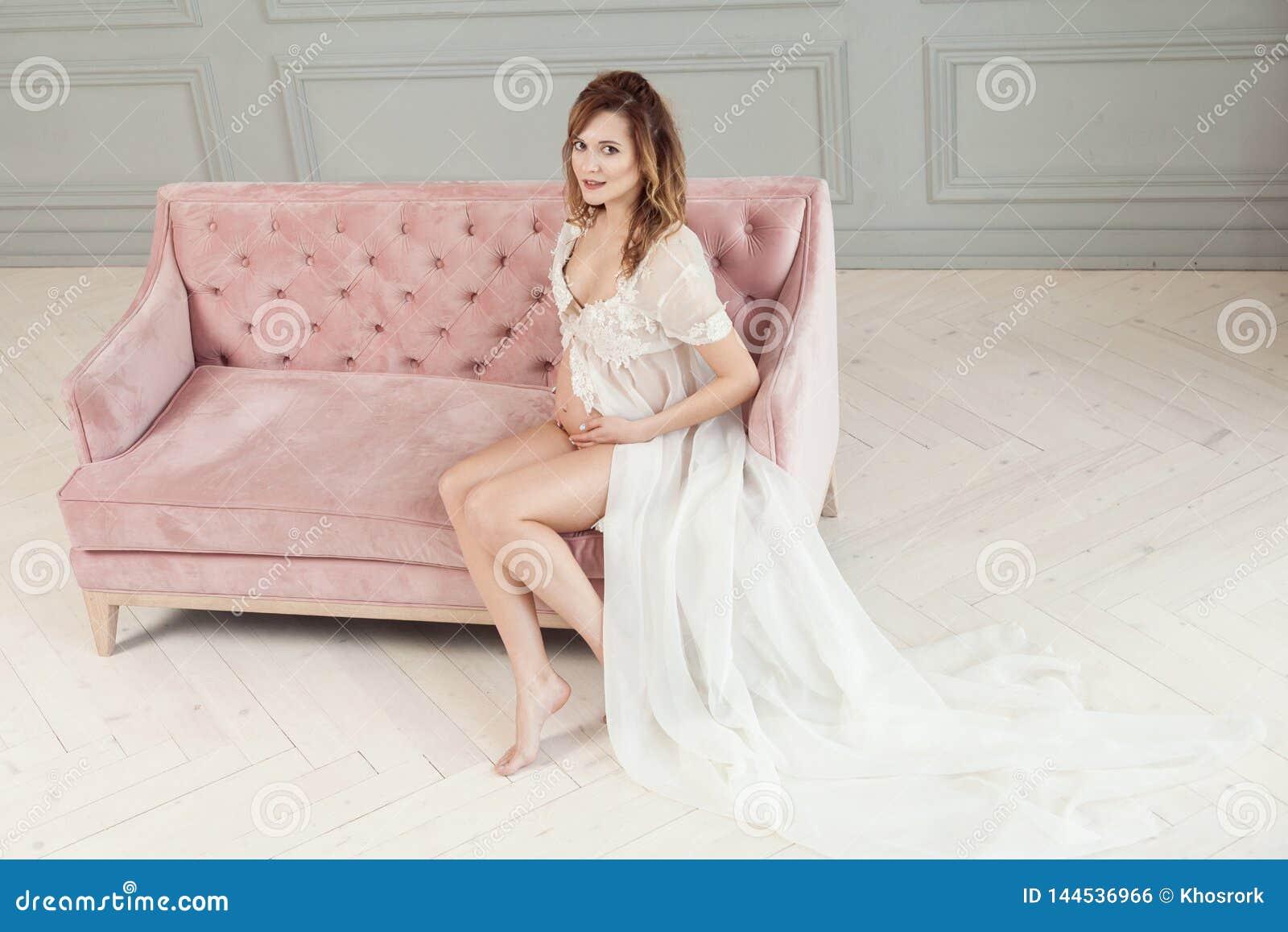 白色礼服peignoir的美丽的年轻孕妇坐桃红色沙发,显示她的赤裸腹部,看照相机