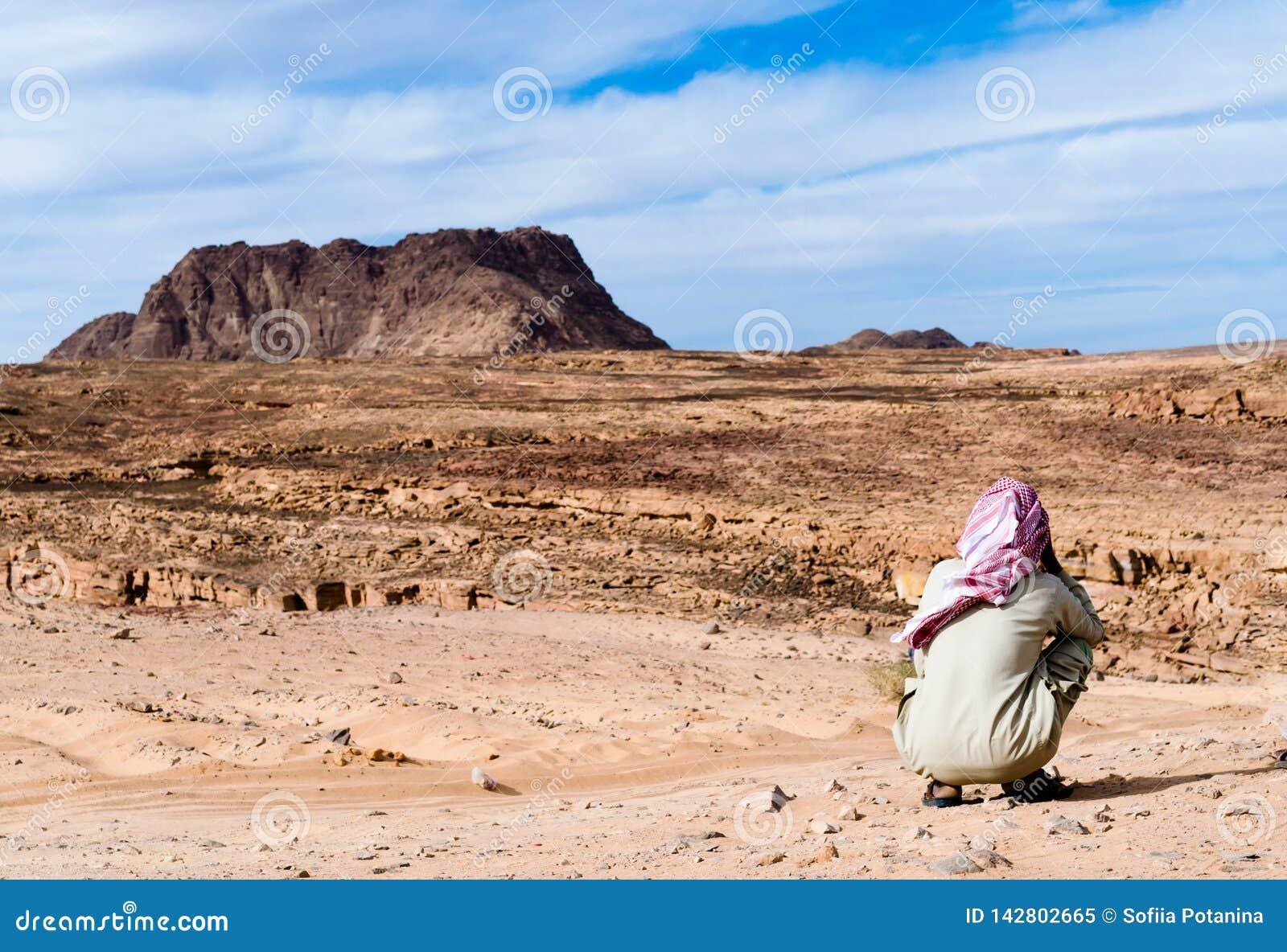 白色红色围巾的流浪者在反对山和天空蔚蓝背景的沙漠在埃及宰海卜南西奈