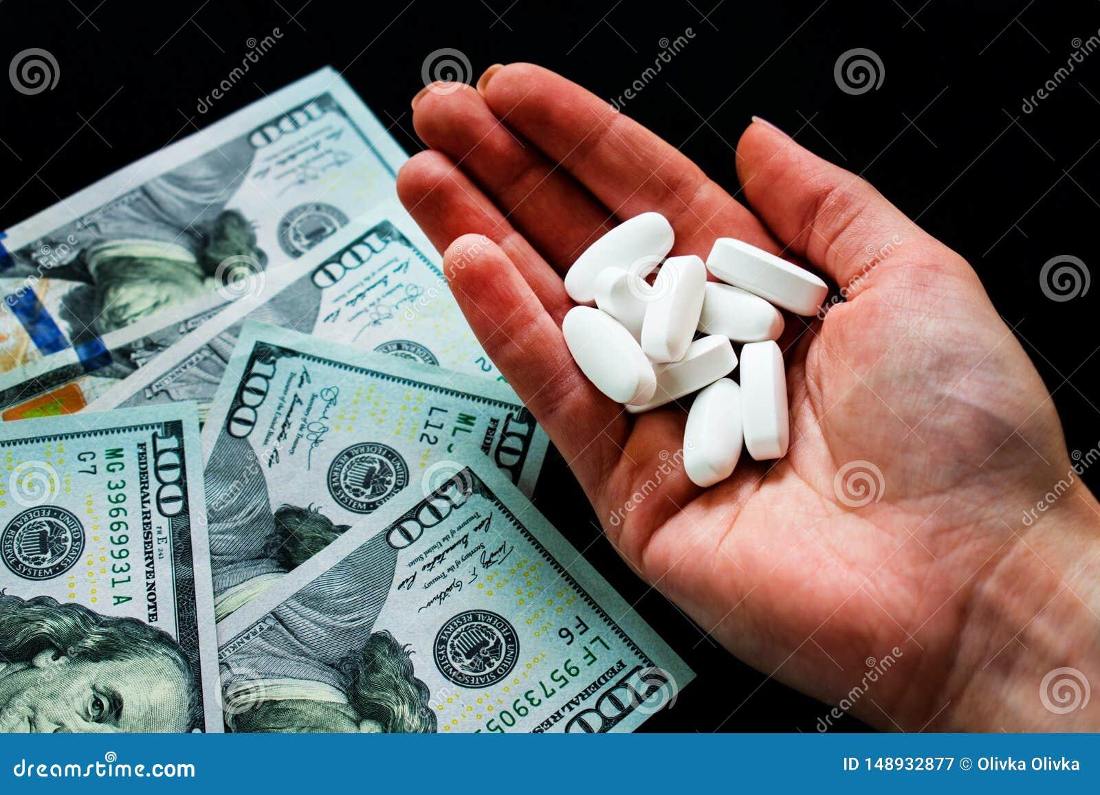 白色药片在手中和dolary在黑背景 很多荧光的药片