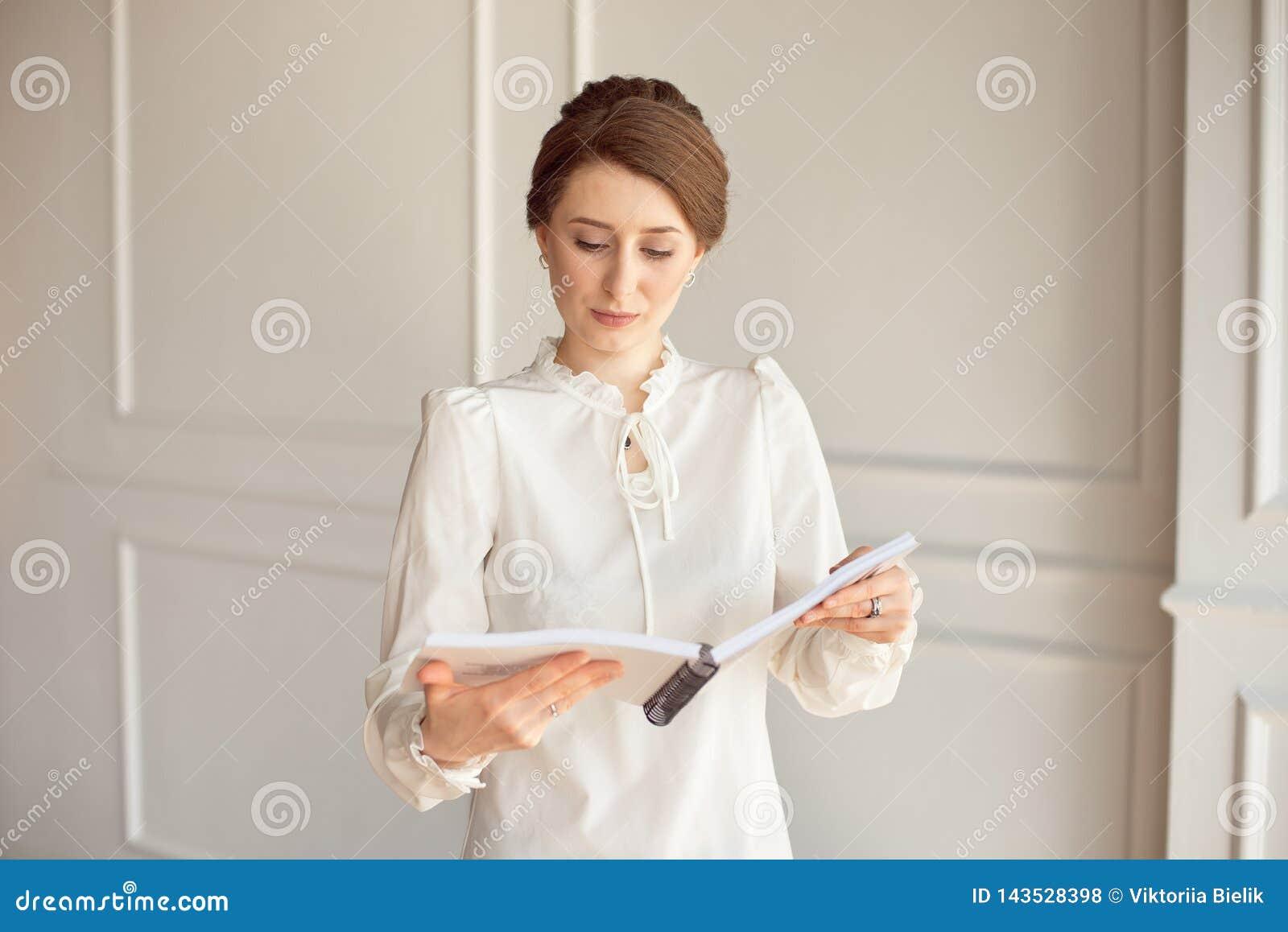 白色衬衫和黑长裤的女商人在手上看文件