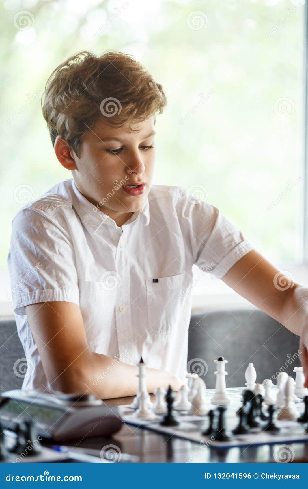 白色衬衫的逗人喜爱,聪明,年轻男孩在教室下在棋枰的棋 教育,爱好,训练