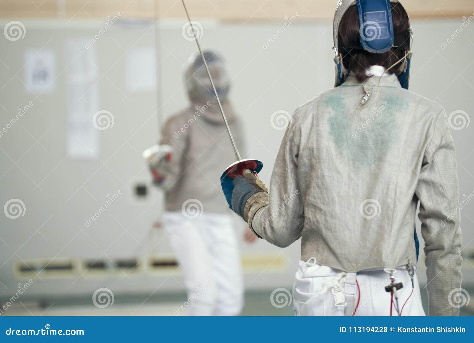 白色防护衣裳的两个少年击剑者战斗在操刀的比赛的