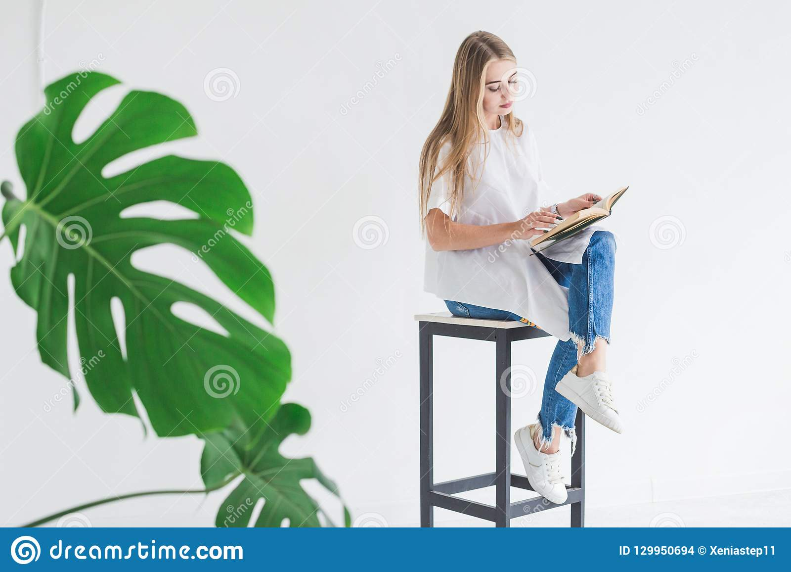 白色T恤和蓝色牛仔裤的读书的一个年轻时髦的白肤金发的女孩的画象在白色背景