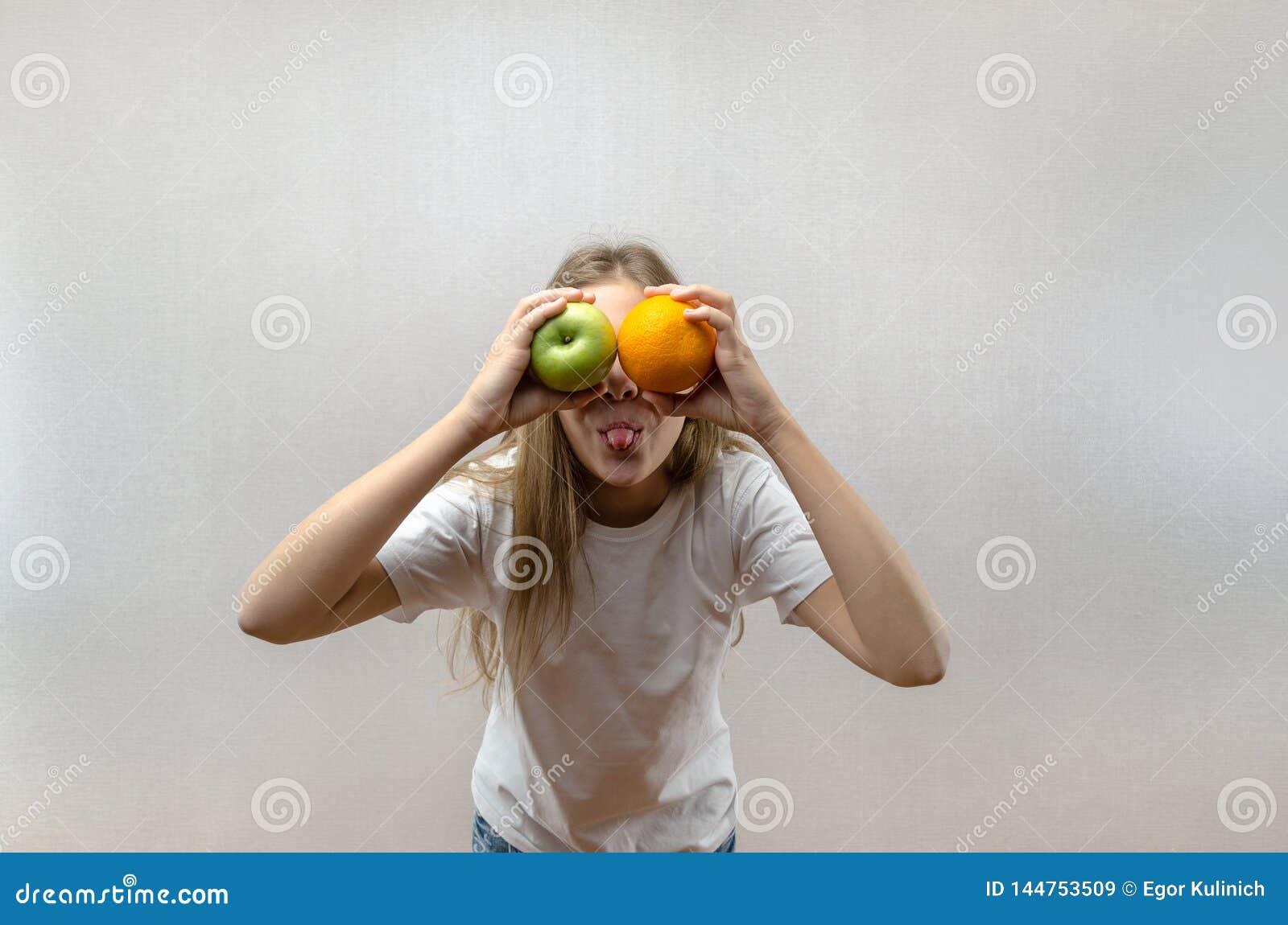 白色T恤的一个美丽的白肤金发的女孩显示她的舌头和拿着苹果和桔子 学童的健康食品