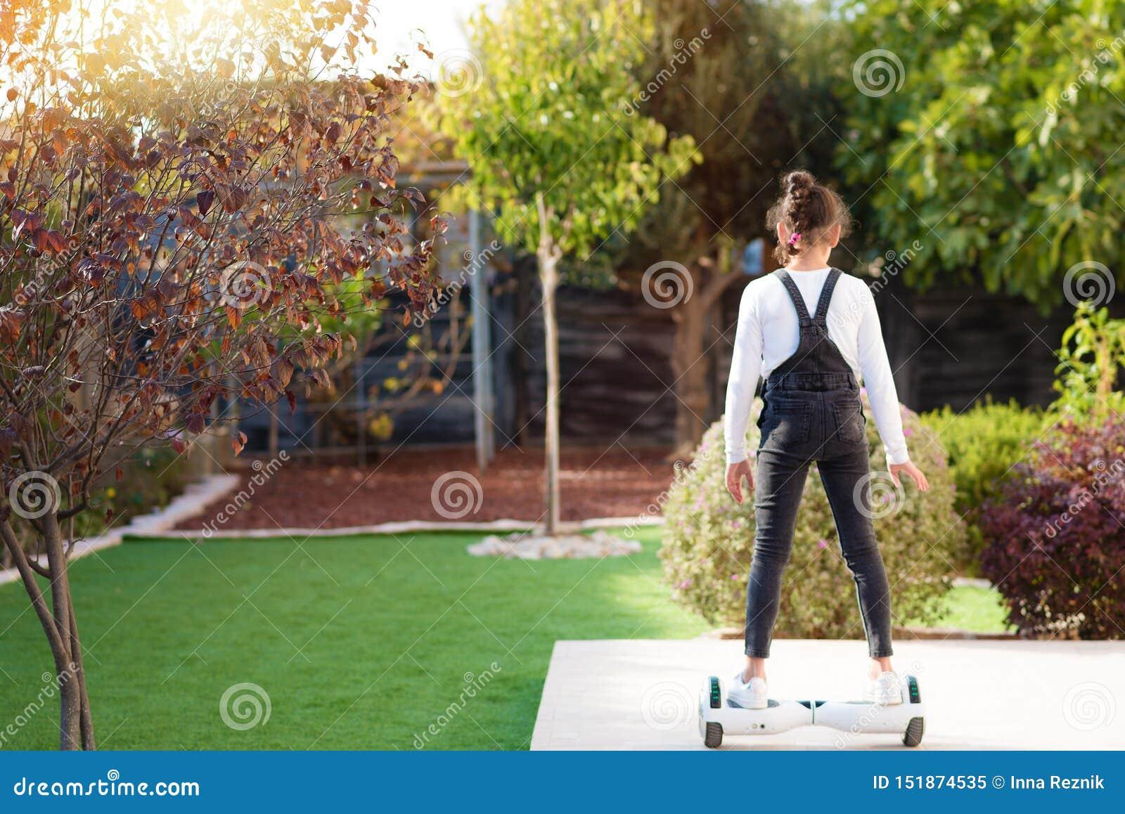 的女孩乘坐一辆电滑行车的后面观点室外 在Hoverboard的年轻少年平衡