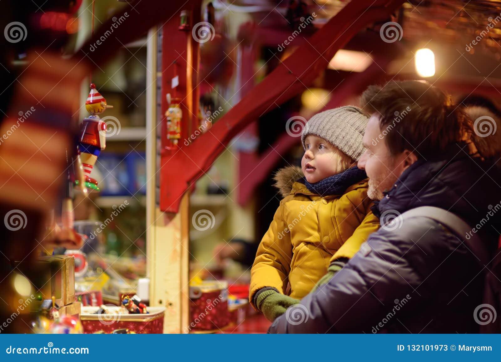 的小男孩和有他的父亲在Xmas市场上的美妙的时间