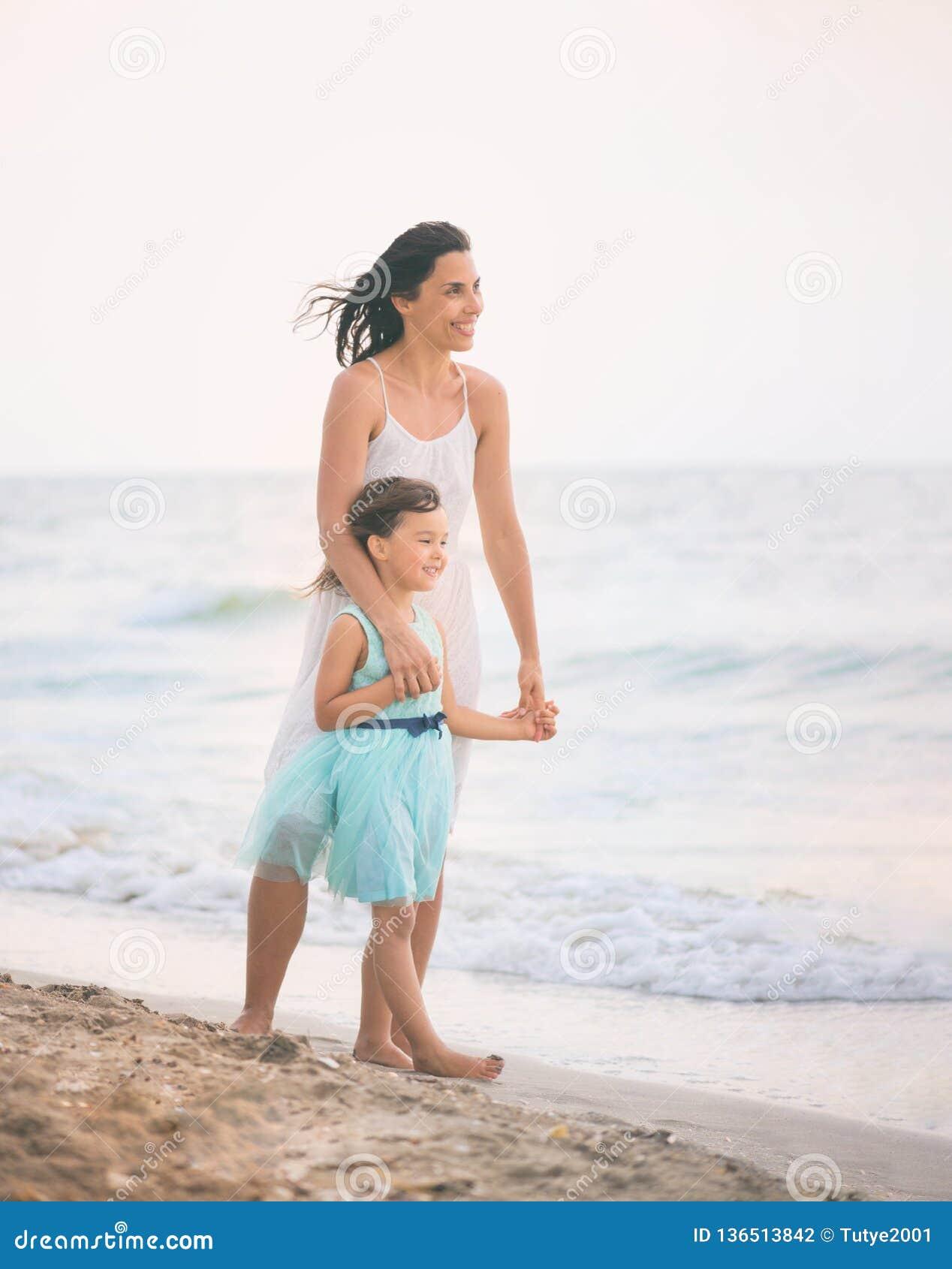 的母亲和获得她的女儿在海滩的乐趣