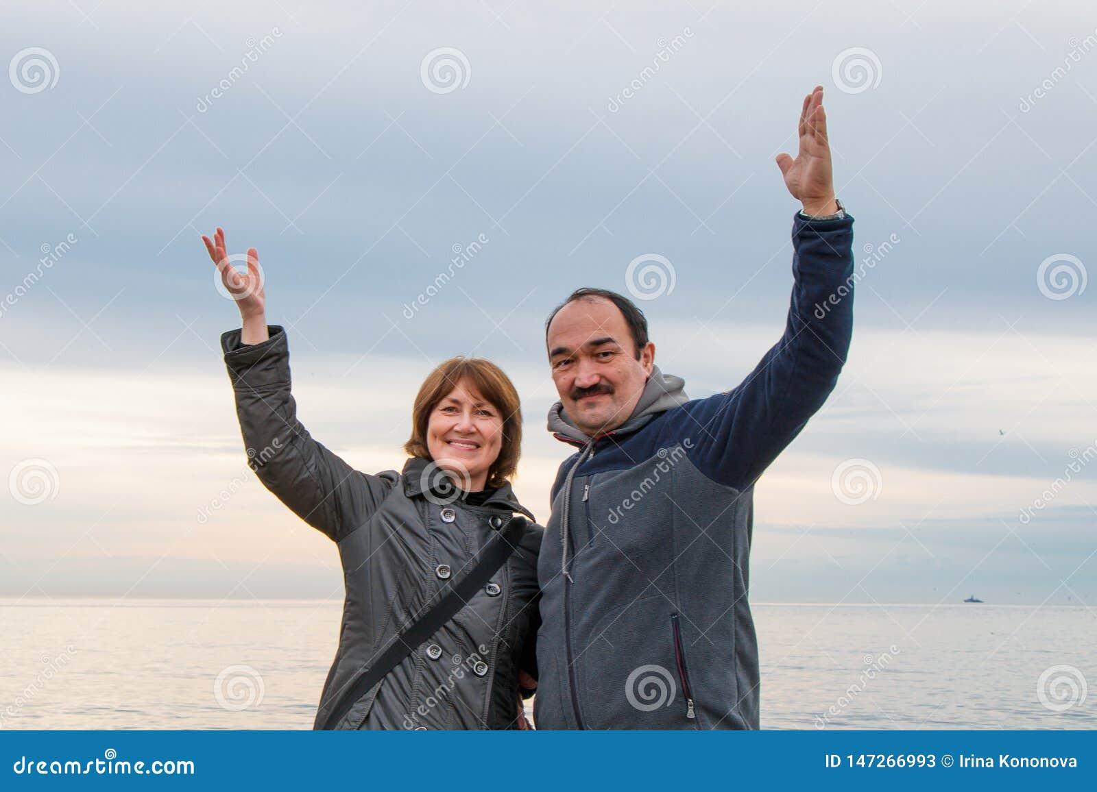 的男人和附近站立的妇女举了他们的在问候的手 海和天空在背景中