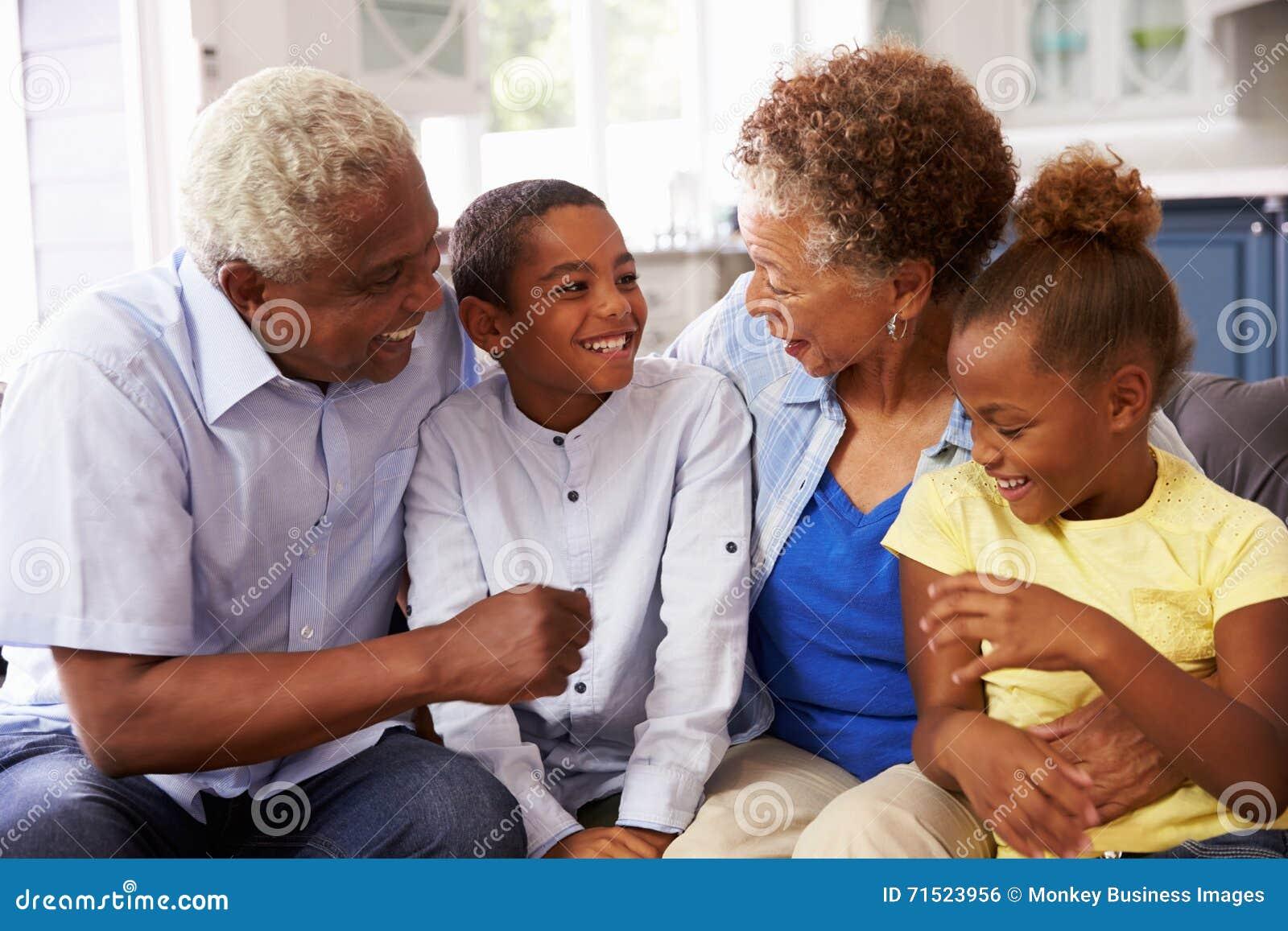 的祖父母和在家放松他们的年轻的孙