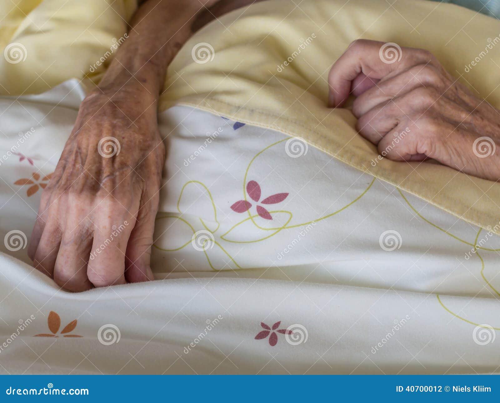 一名非常老和皮包骨头的妇女的手在床上.