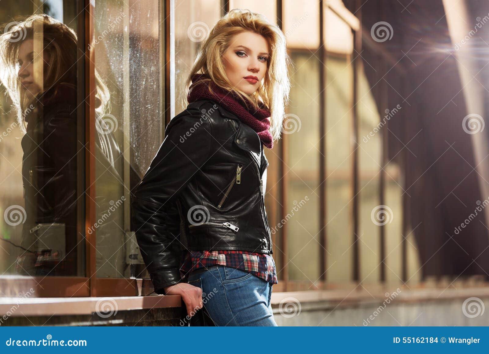 年轻皮夹克的时尚白肤金发的妇女在购物中心窗口