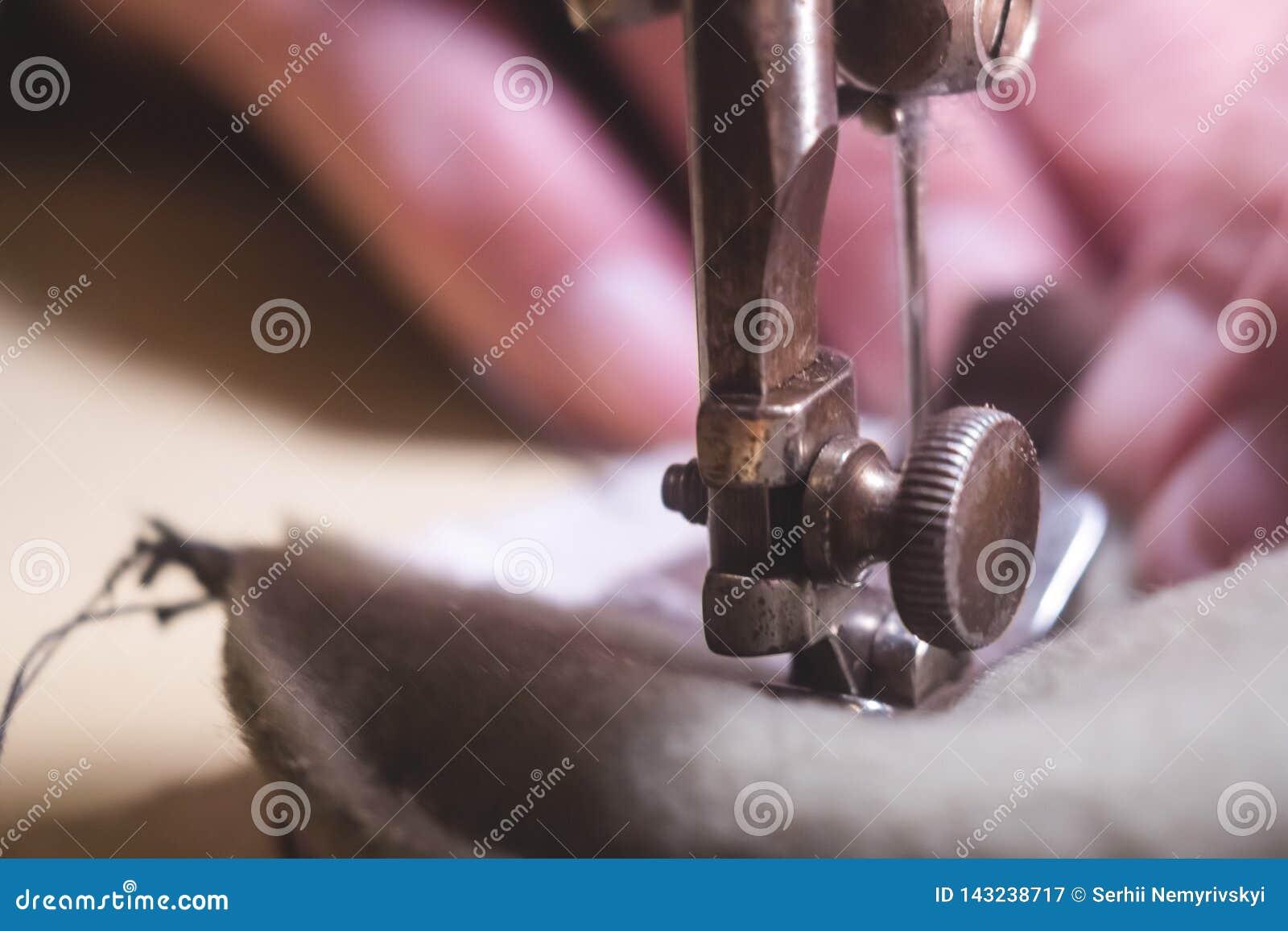 皮带的缝合的过程 在缝合后的老人的手 皮革车间 纺织品葡萄酒缝合工业