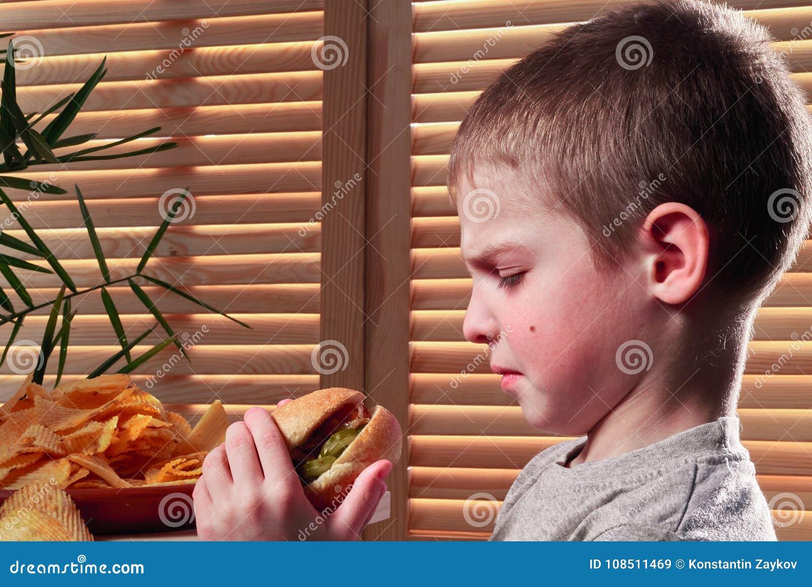 皱眉的男孩看热狗 孩子凝视充满憎恶在咖啡馆的无味的食物 快餐