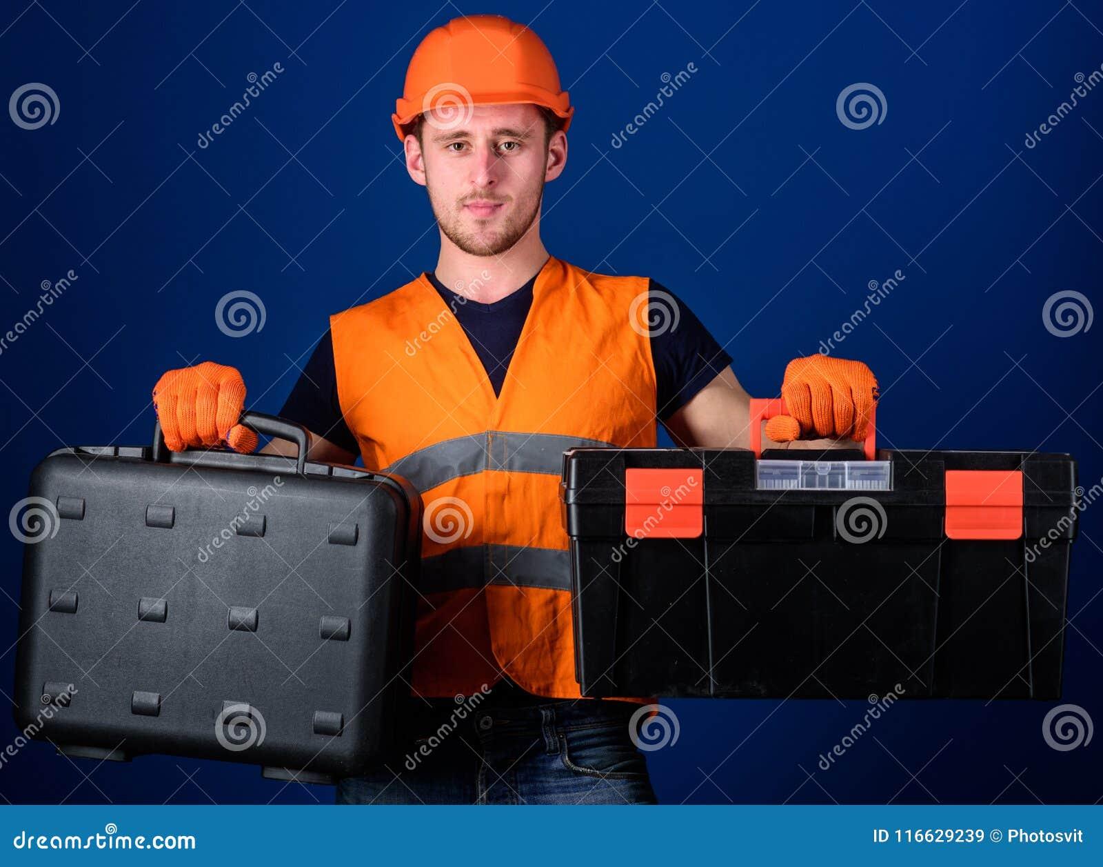 盔甲的人,安全帽拿着工具箱和手提箱有工具的,蓝色背景 工作者,修理匠,安装工,建造者