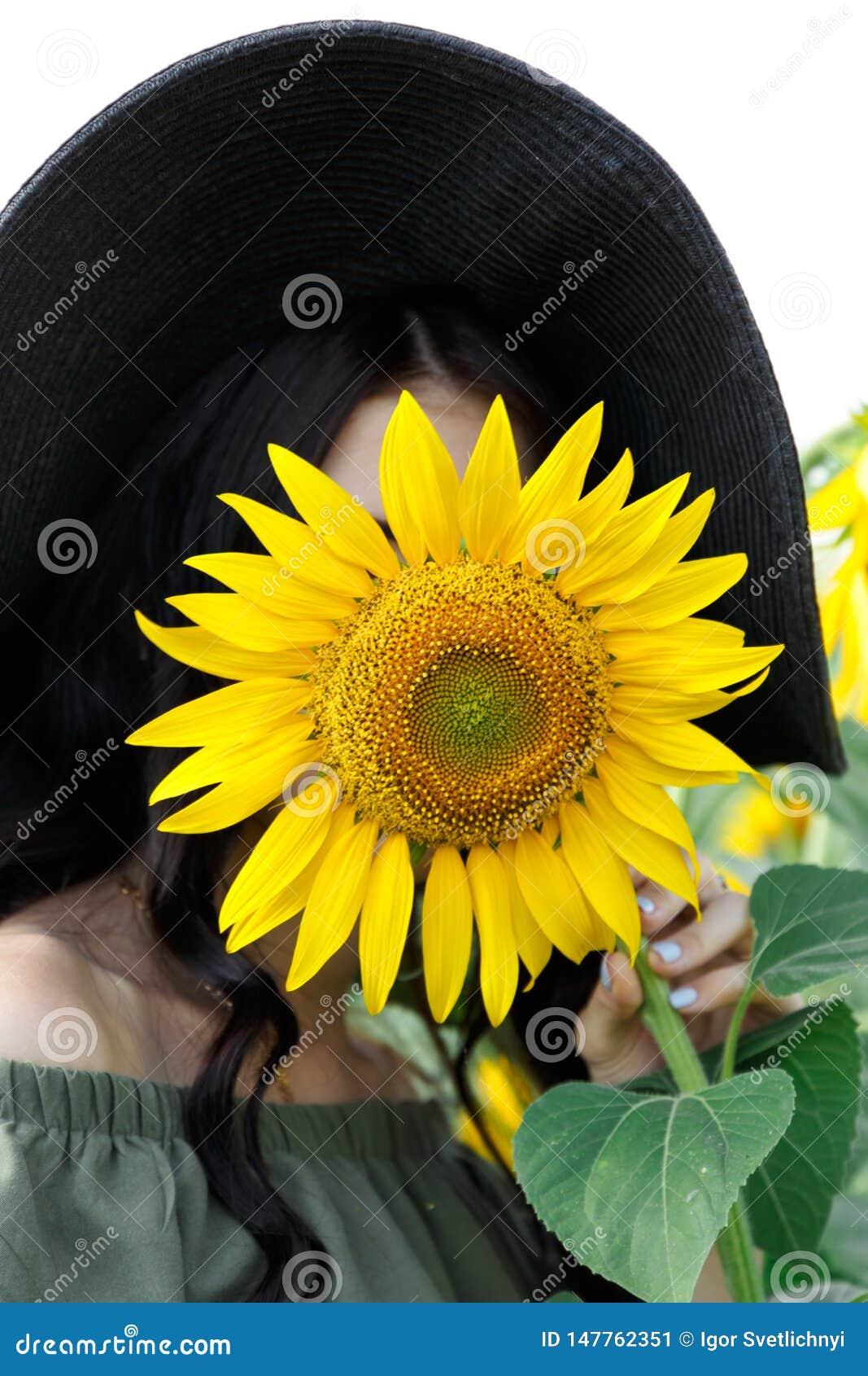 盖她的面孔的美女的画象用向日葵 自然,夏天休假,假期 有长发的妇女在礼服