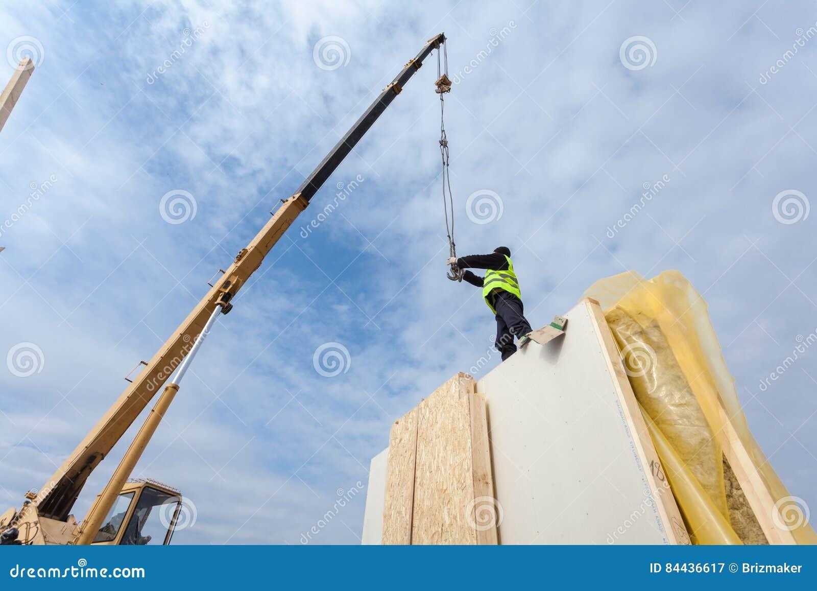 盖屋顶的人有安装结构被绝缘的盘区SIP的起重机的建造者工作者 修造的新的框架省能源的房子