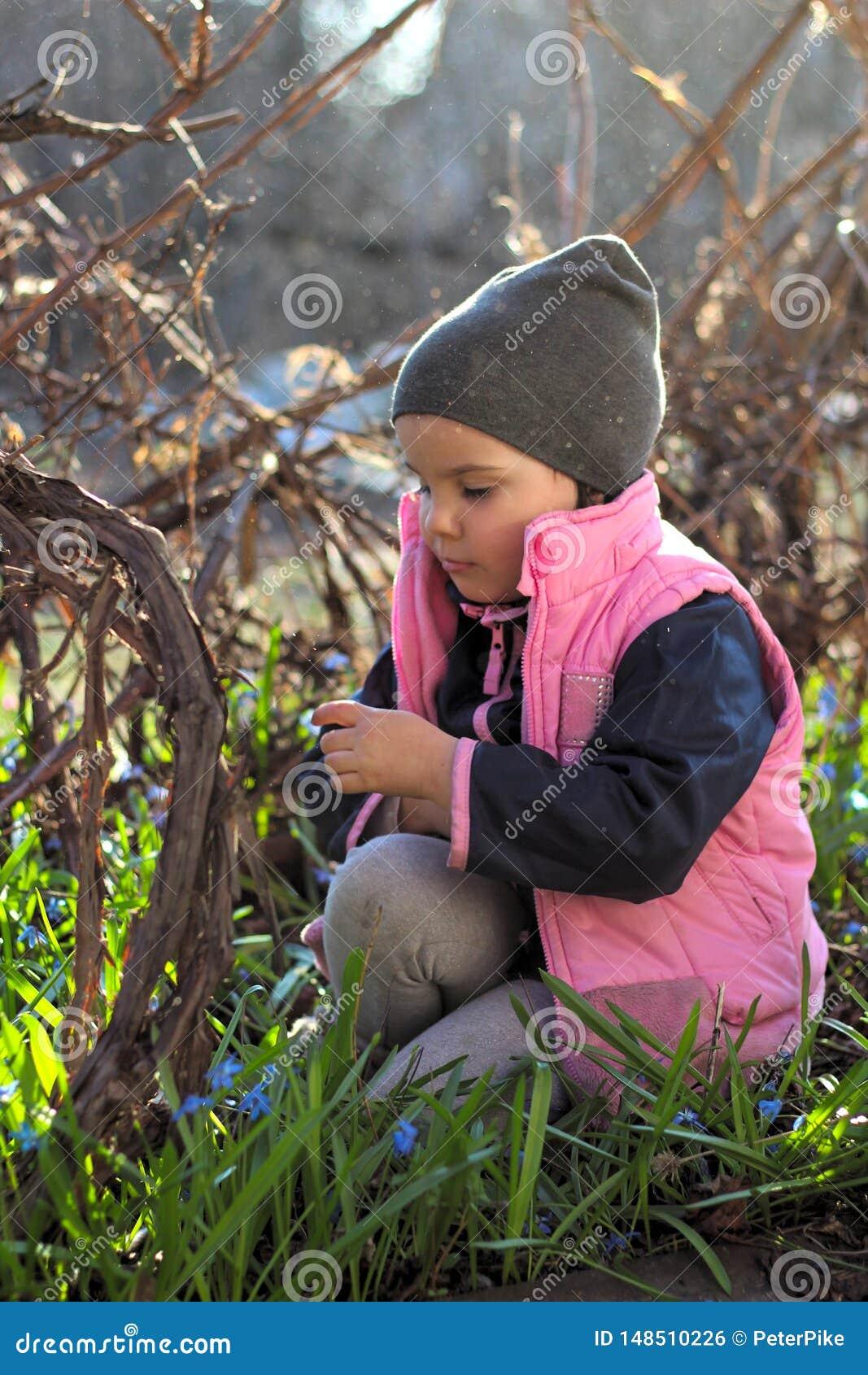盖帽的哀伤,被触犯的,温暖地加工好的女孩坐她的在蓝色snowdrops中花的膝盖在葡萄园里