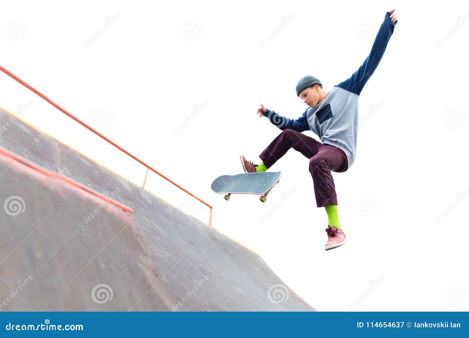 盖帽的少年溜冰板者做与一个跃迁的一个把戏在skatepark的舷梯 溜冰者和舷梯