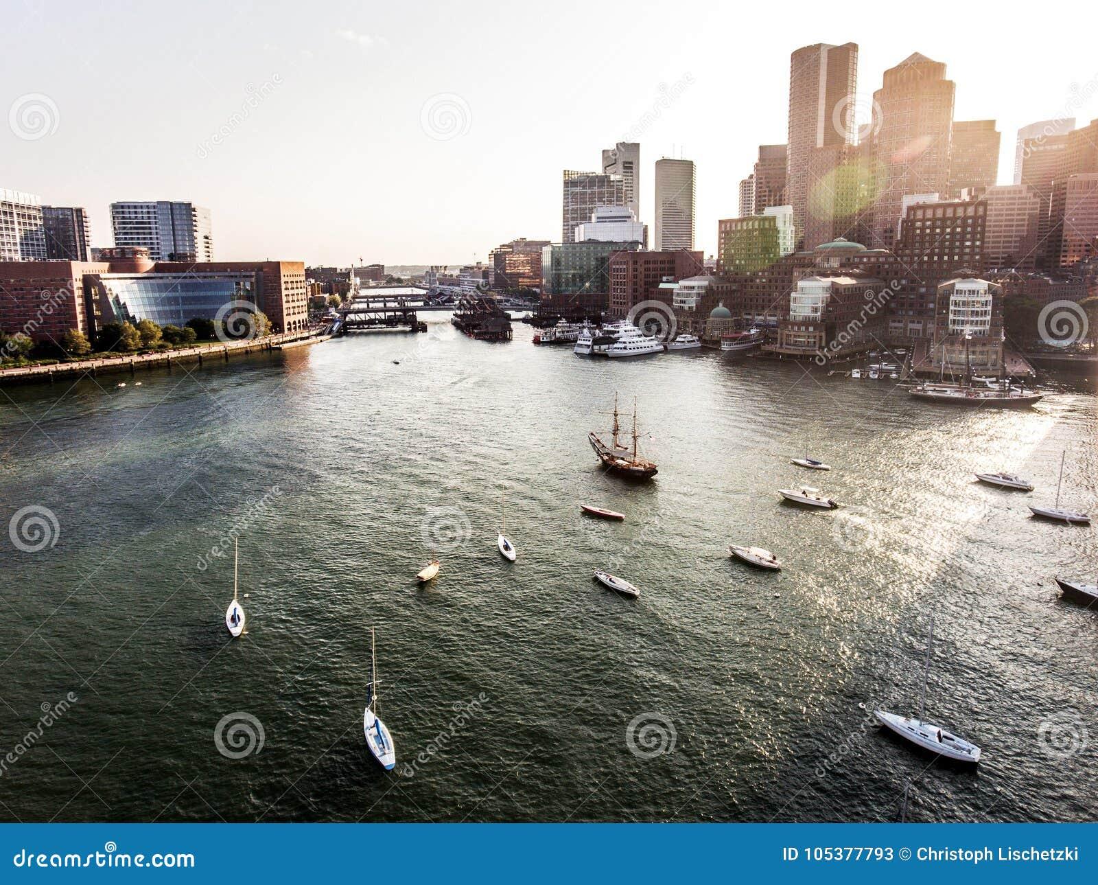 直升机飞行鸟瞰图图象地平线波士顿麻省,在日落期间的美国在摩天大楼后临近江边海湾