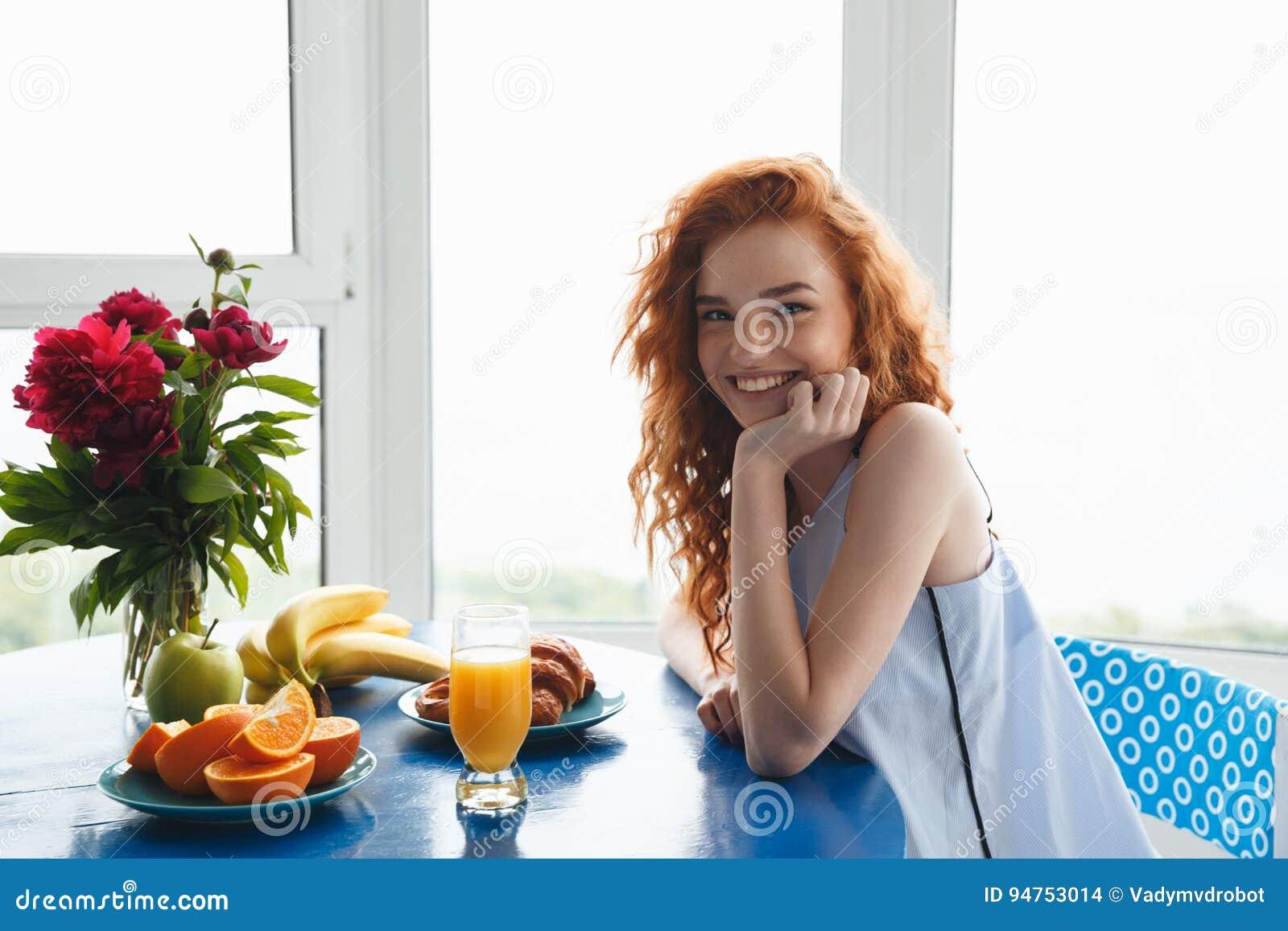 相当在花和果子附近的快乐的年轻红头发人夫人