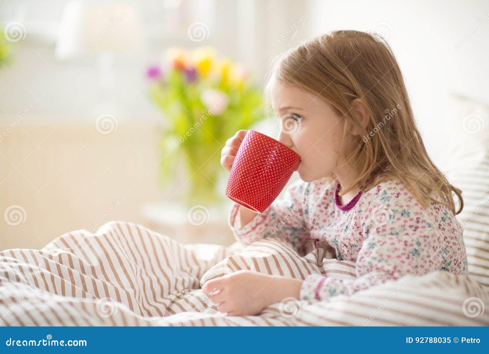 相当放置在床饮料茶的病的小孩女孩