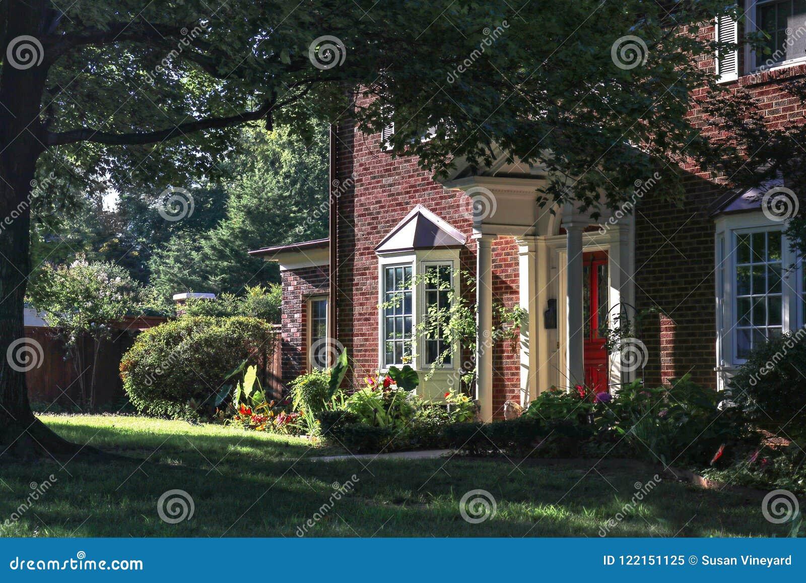 相当有凸出的三面窗的二层的砖房子和从侧角的高大的树木和红色前门看法在与hig的黄昏