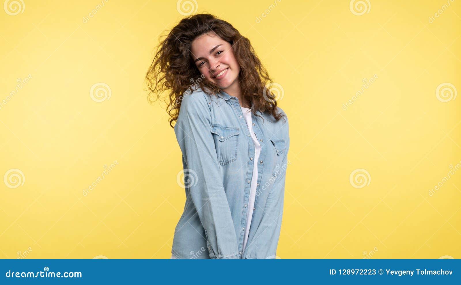 相当有卷发的shuy深色的妇女在黄色背景