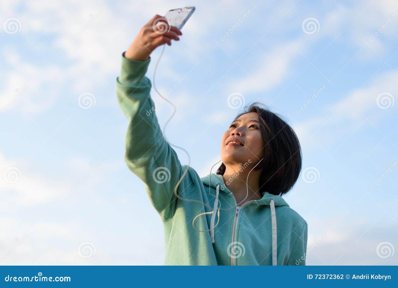 相当有采取selfie的短发的逗人喜爱的日本妇女画象室外使用她的电话 蓝色多云天空背景