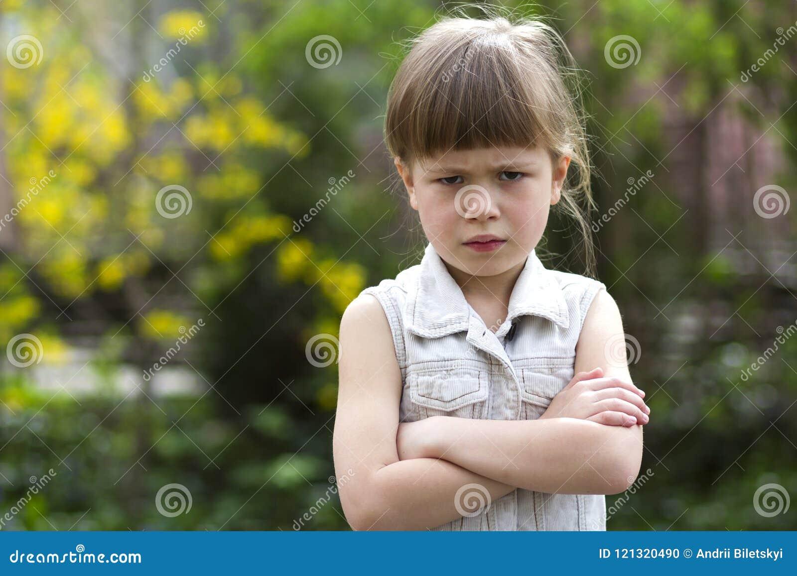 相当白色无袖的礼服的滑稽的喜怒无常的矮小的白肤金发的学龄前女孩调查感到的照相机恼怒和不满意在blurre