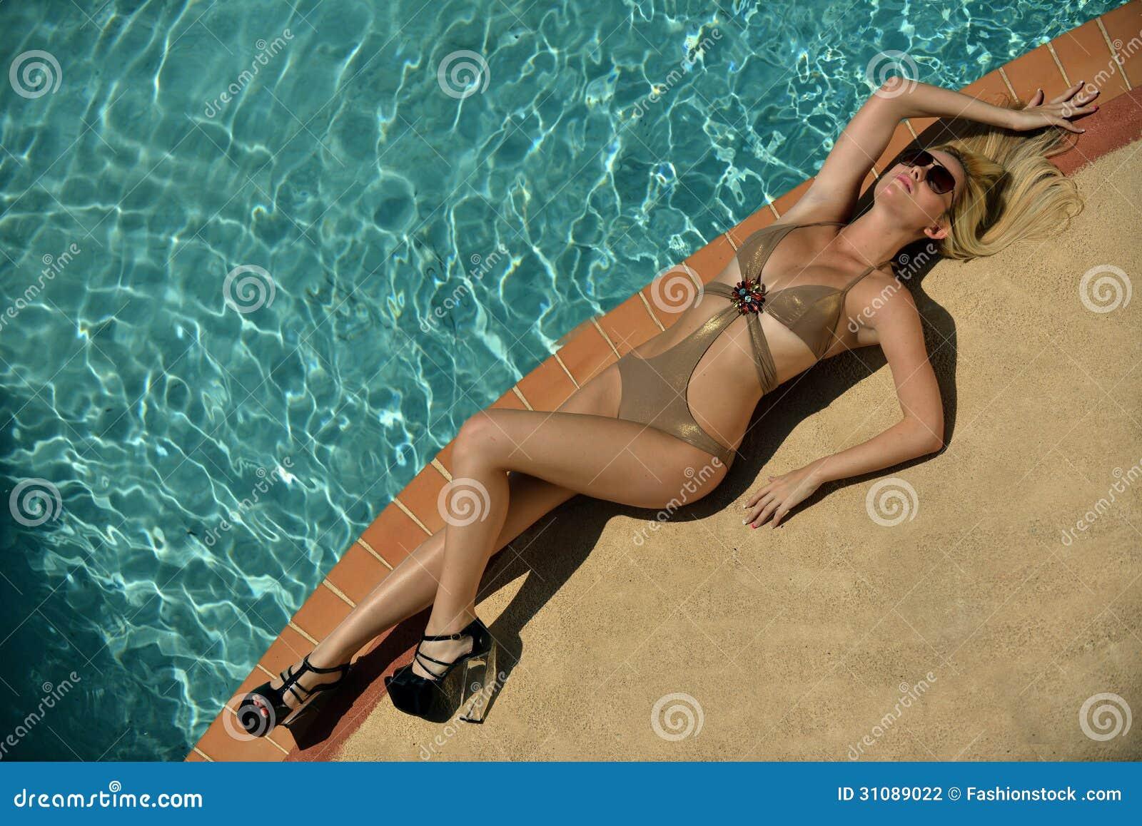相当躺下在游泳池边缘的白肤金发的模型
