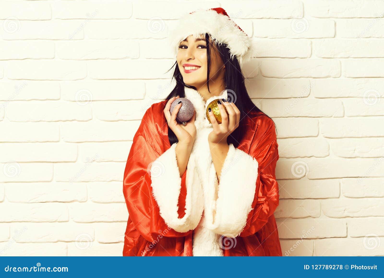 相当逗人喜爱的性感的圣诞老人女孩或微笑的深色的妇女新年毛线衣和帽子的拿着圣诞节或xmas五颜六色的球