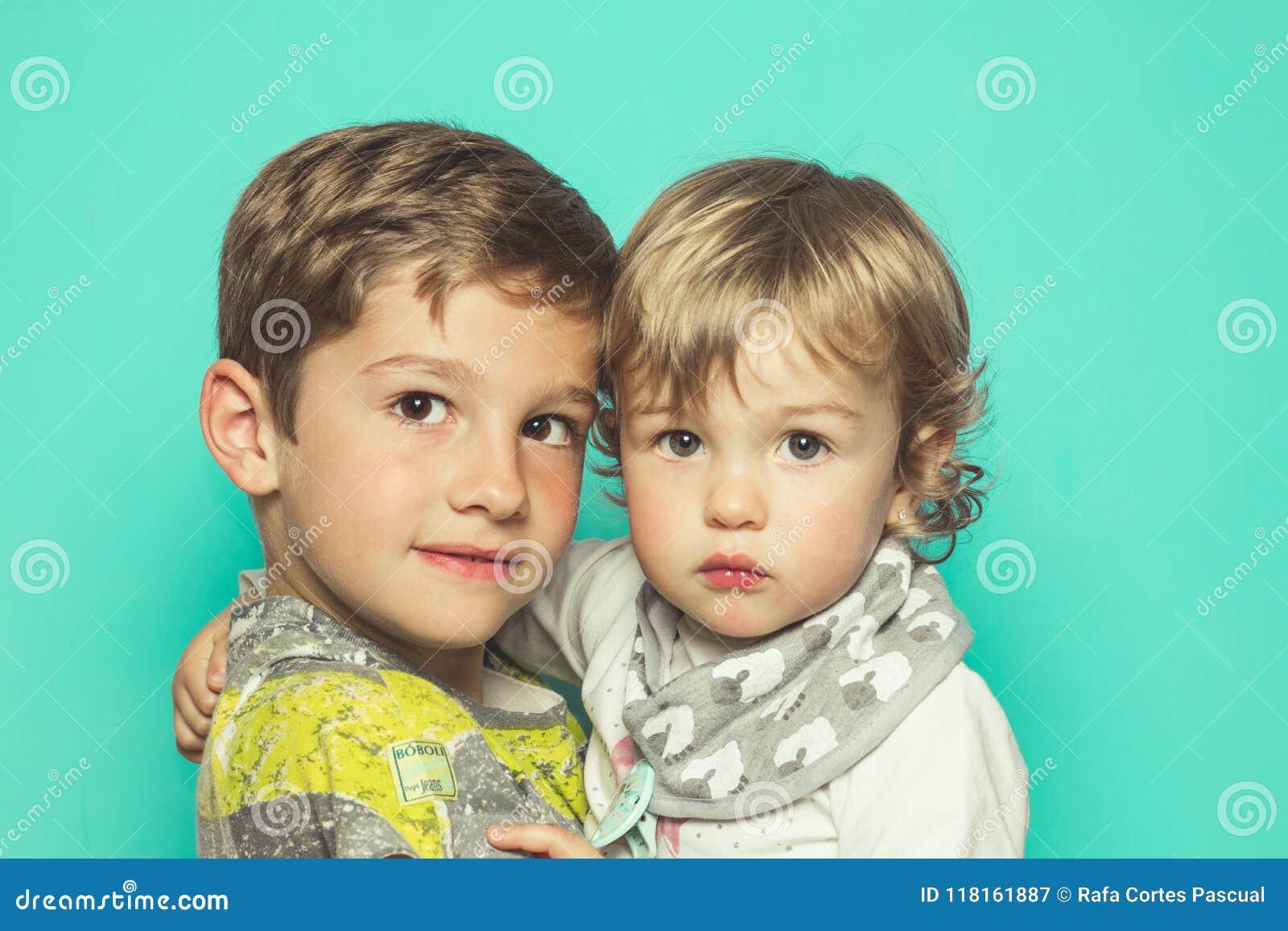 看与轻微的微笑的一个小男孩和一个小女孩的画象照相机