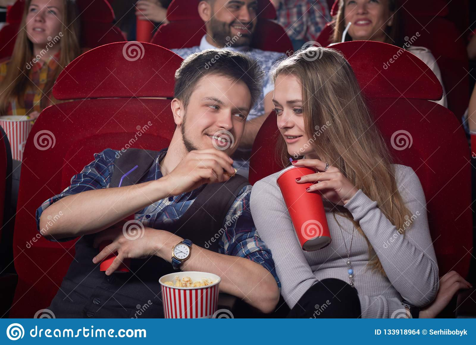 看从逗人喜爱的夫妇的旁边在戏院的
