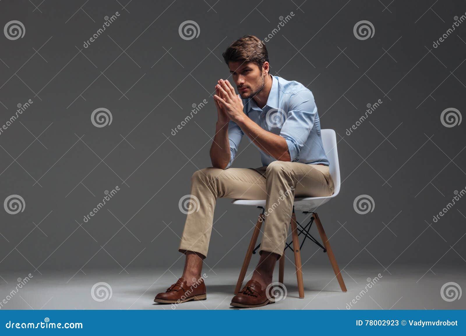 看体贴的英俊的年轻的人坐椅子和