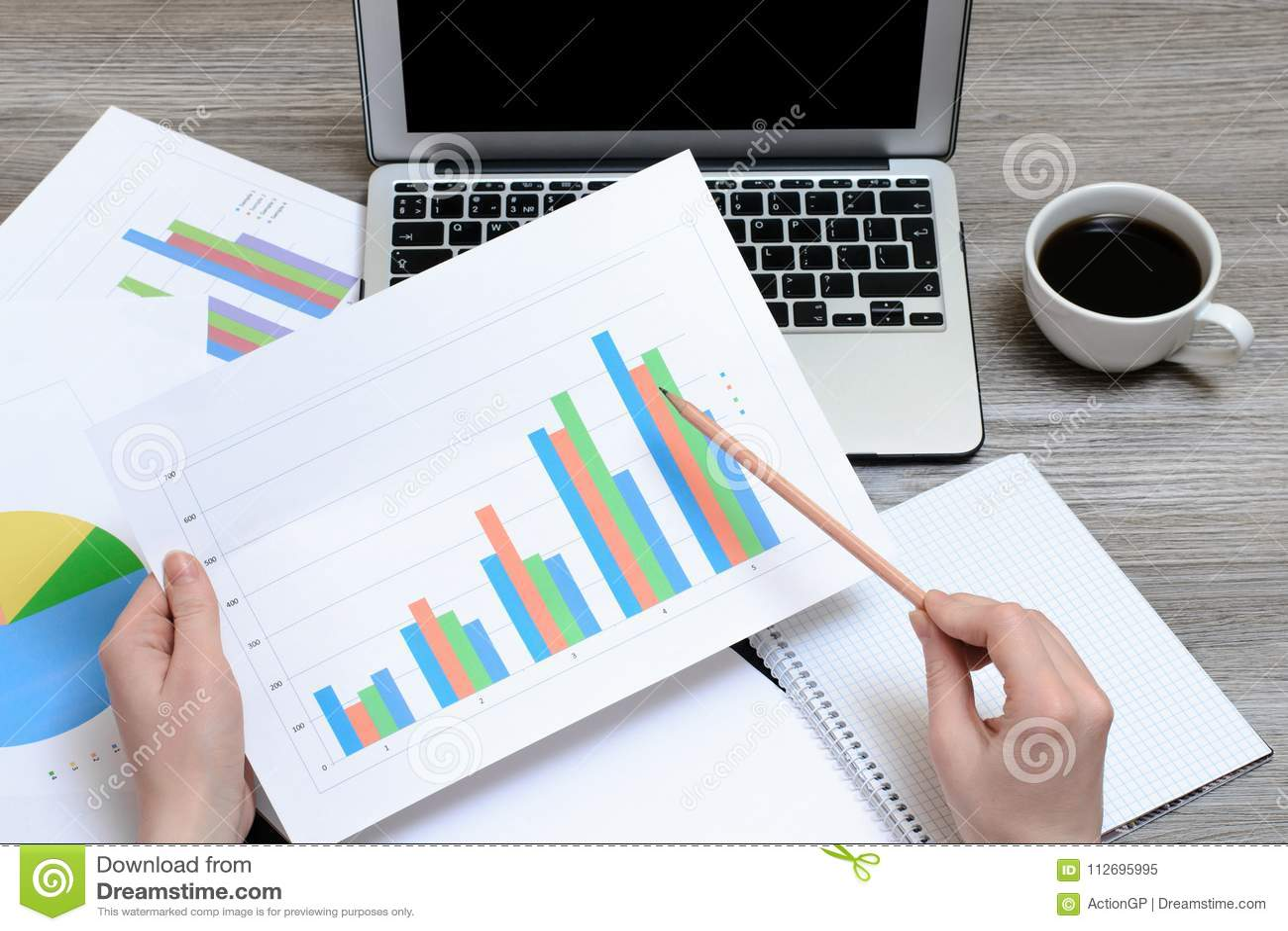 看图表的工作者 在拿着图表,膝上型计算机,咖啡的手上的顶视图,工作场所工作站,最佳项目的进展