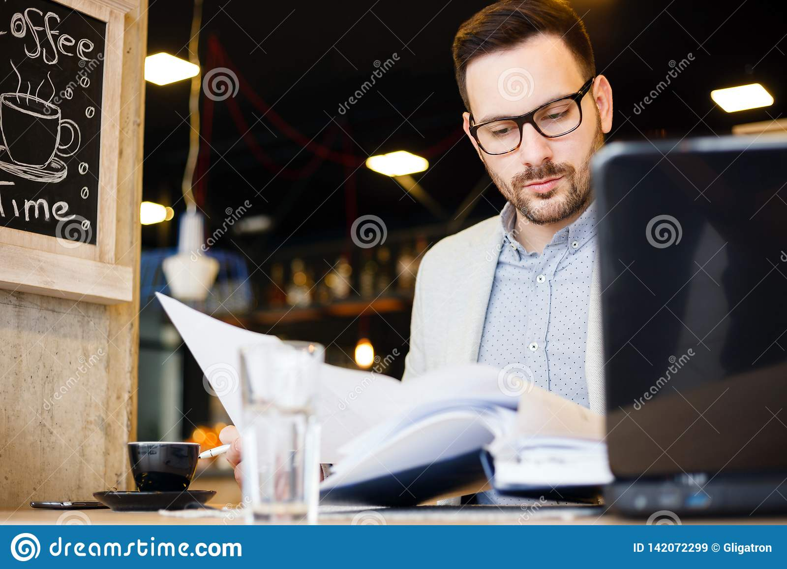 看在修造的计划的年轻建筑师,当工作在一个现代咖啡馆时