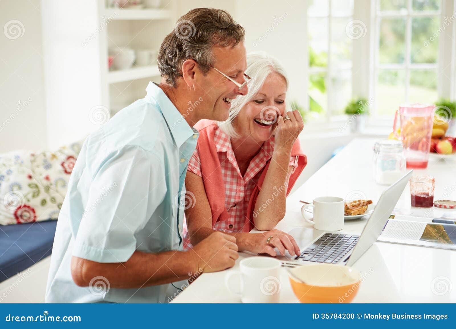看在早餐的中世纪夫妇膝上型计算机