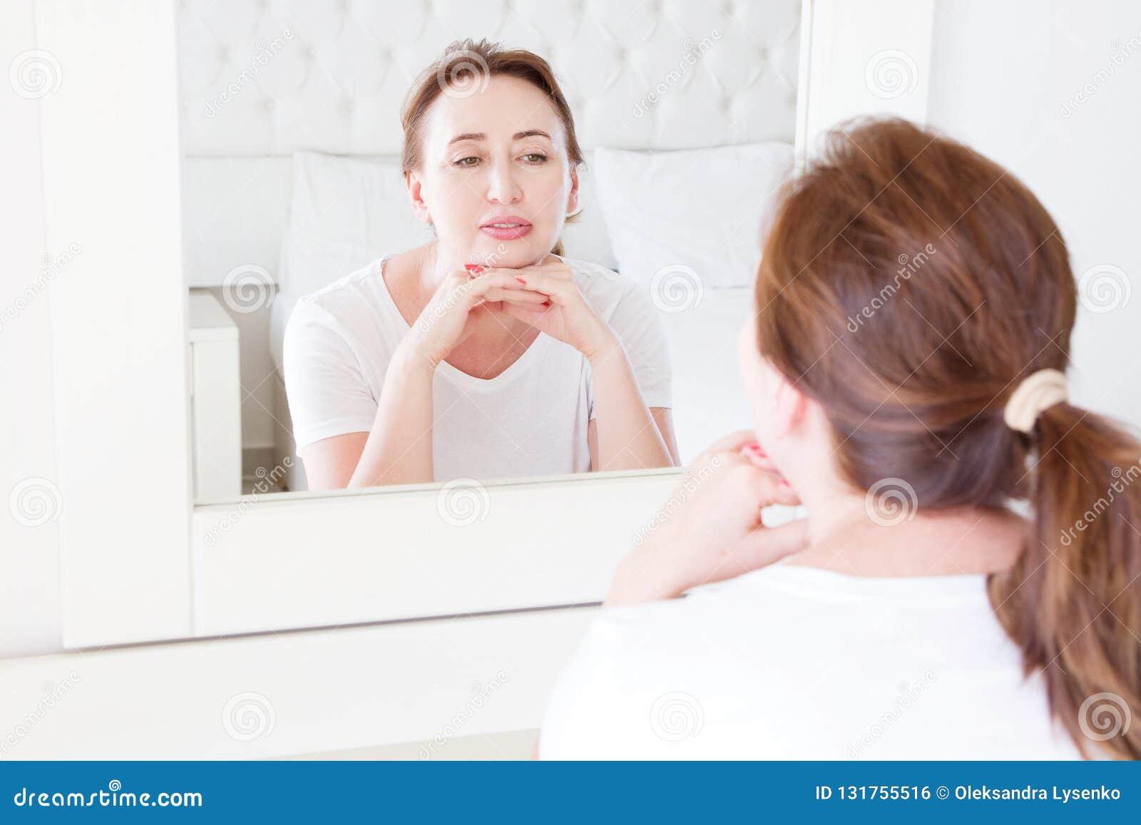 看在面孔的镜子的中年妇女 皱痕和防皱护肤概念 选择聚焦