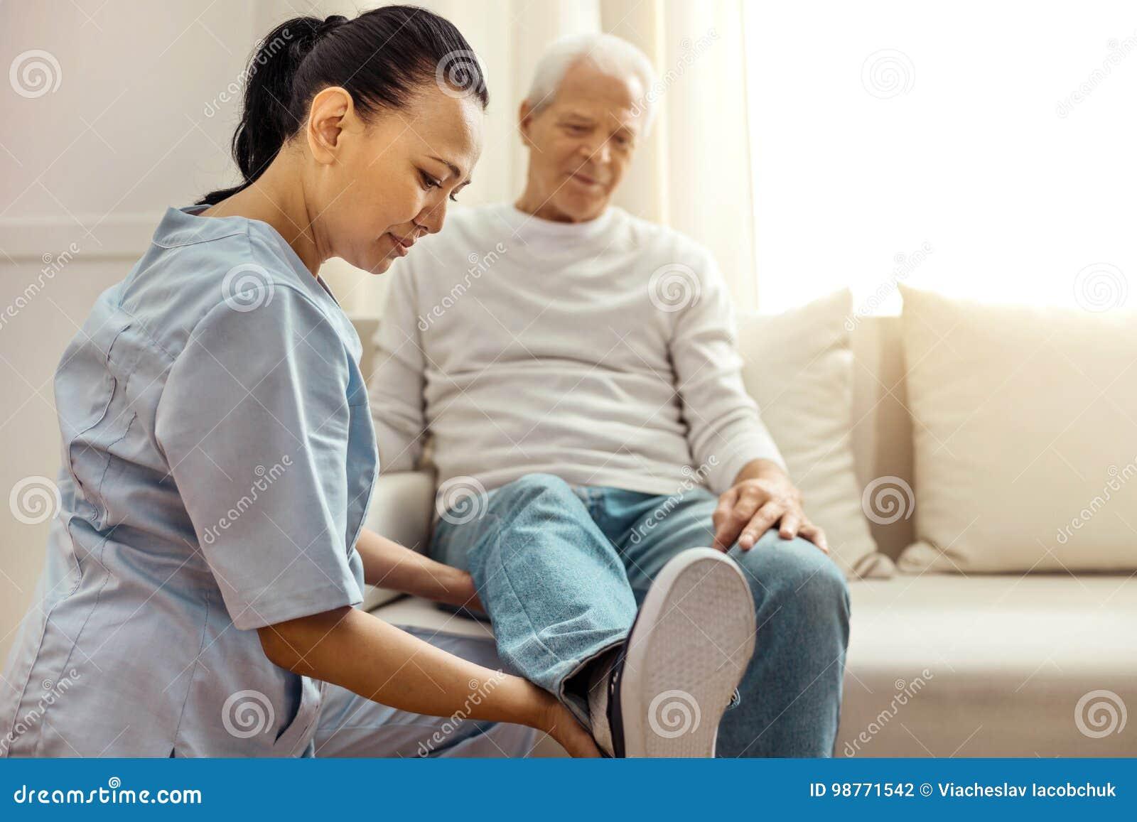 看她的患者腿的高兴宜人的护士