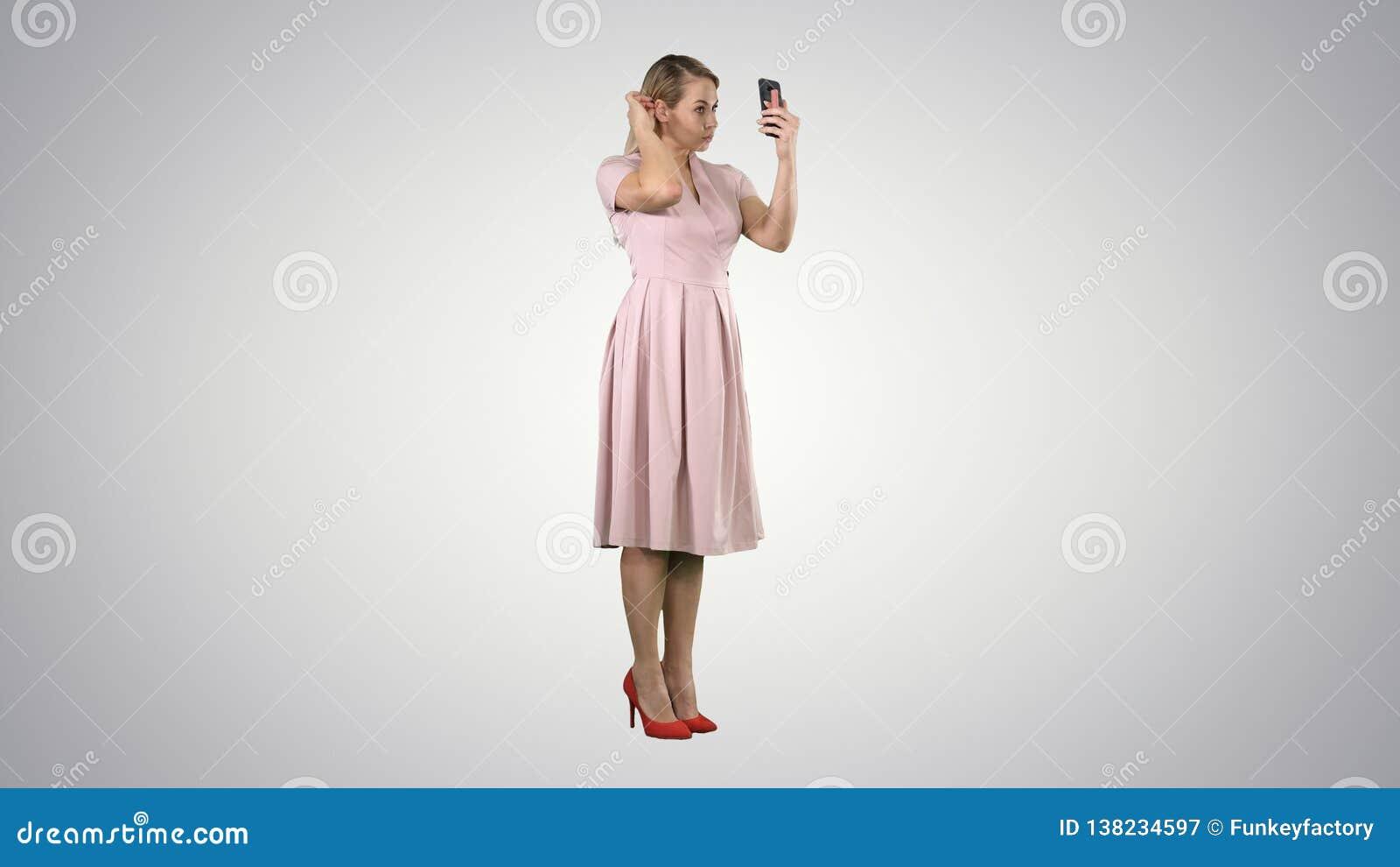 看她自己的秀丽妇女在她的修理她的在梯度背景的智能手机头发