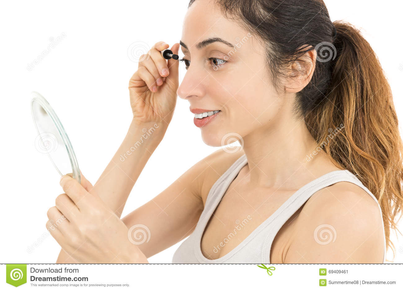 看对镜子和应用染睫毛油的妇女