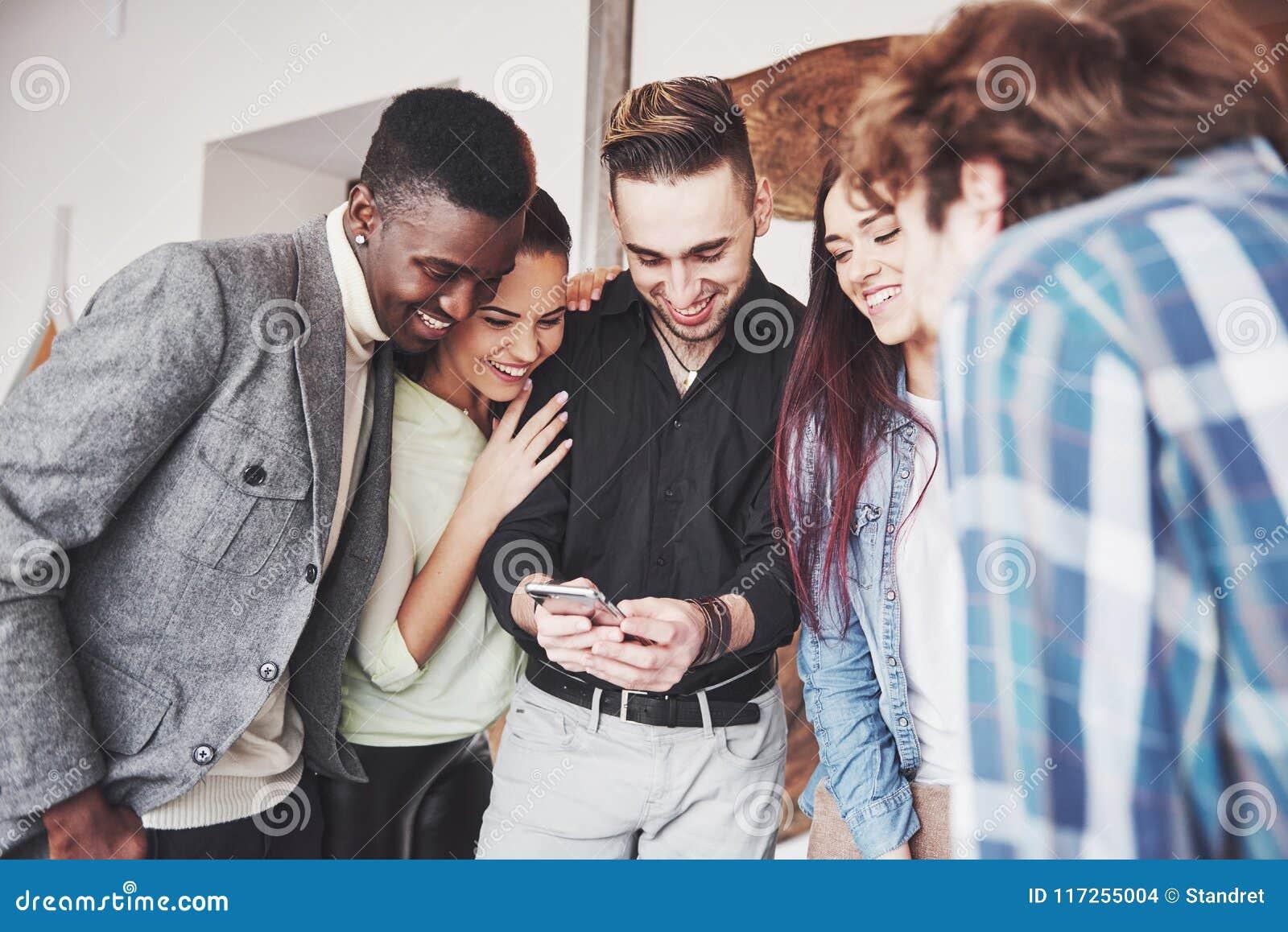 看巧妙的电话的快乐的年轻朋友画象,当坐在咖啡馆时 混合的族种人在餐馆使用