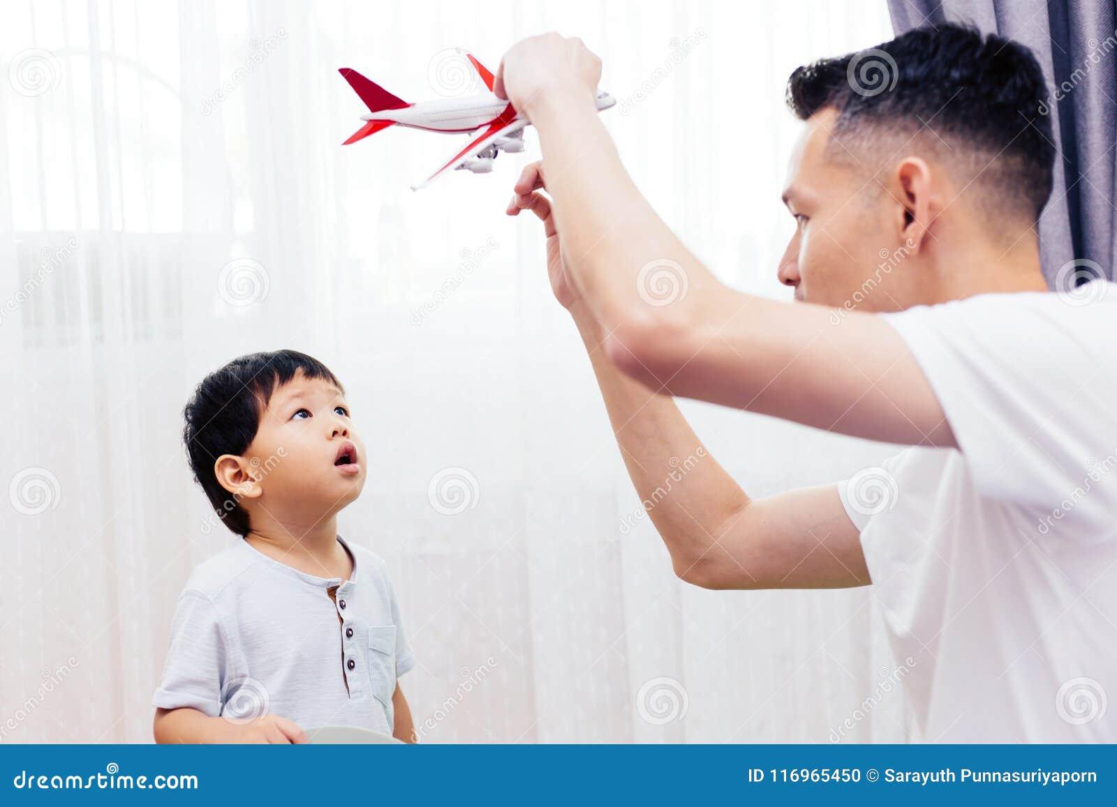 看平面玩具和使用与父亲的好奇孩子 一起演奏玩具的亚洲家庭在家
